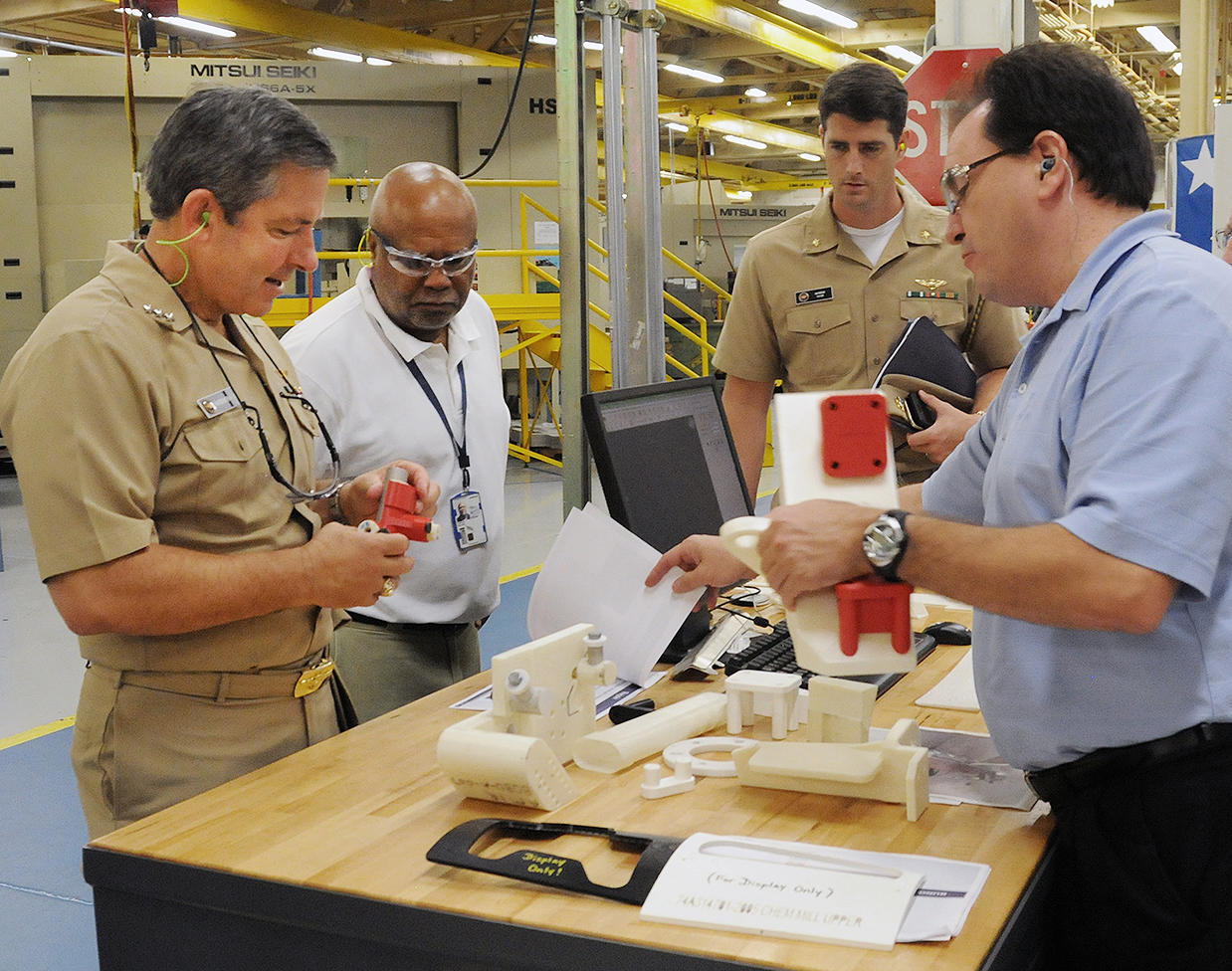 Randall Meeker, right, a mechanical engineering technician and tool designer at Fleet Readiness Center Southeast (FRCSE), explains how he uses a 3-D computer software program and additive manufacturing to build tools and aircraft prototypes to Vice Adm. David Dunaway, commander of Naval Air Systems Command on Aug. 12, 2015. US Navy Photo