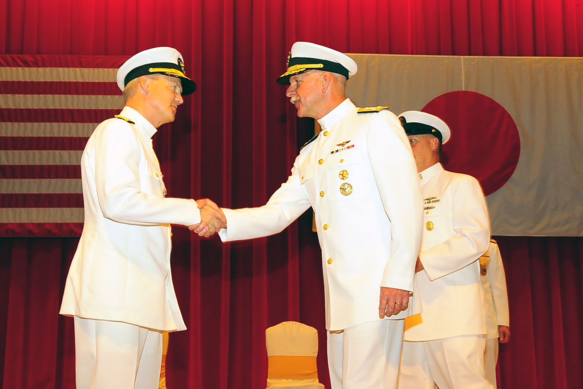 Adm. Scott H. Swift, commander, U.S. Pacific Fleet, congratulates Vice Adm. Robert L. Thomas, commander U.S. 7th Fleet, during a change of command ceremony at Fleet Activities Yokosuka Fleet Theater on Sept. 7, 2015. US Navy photo.