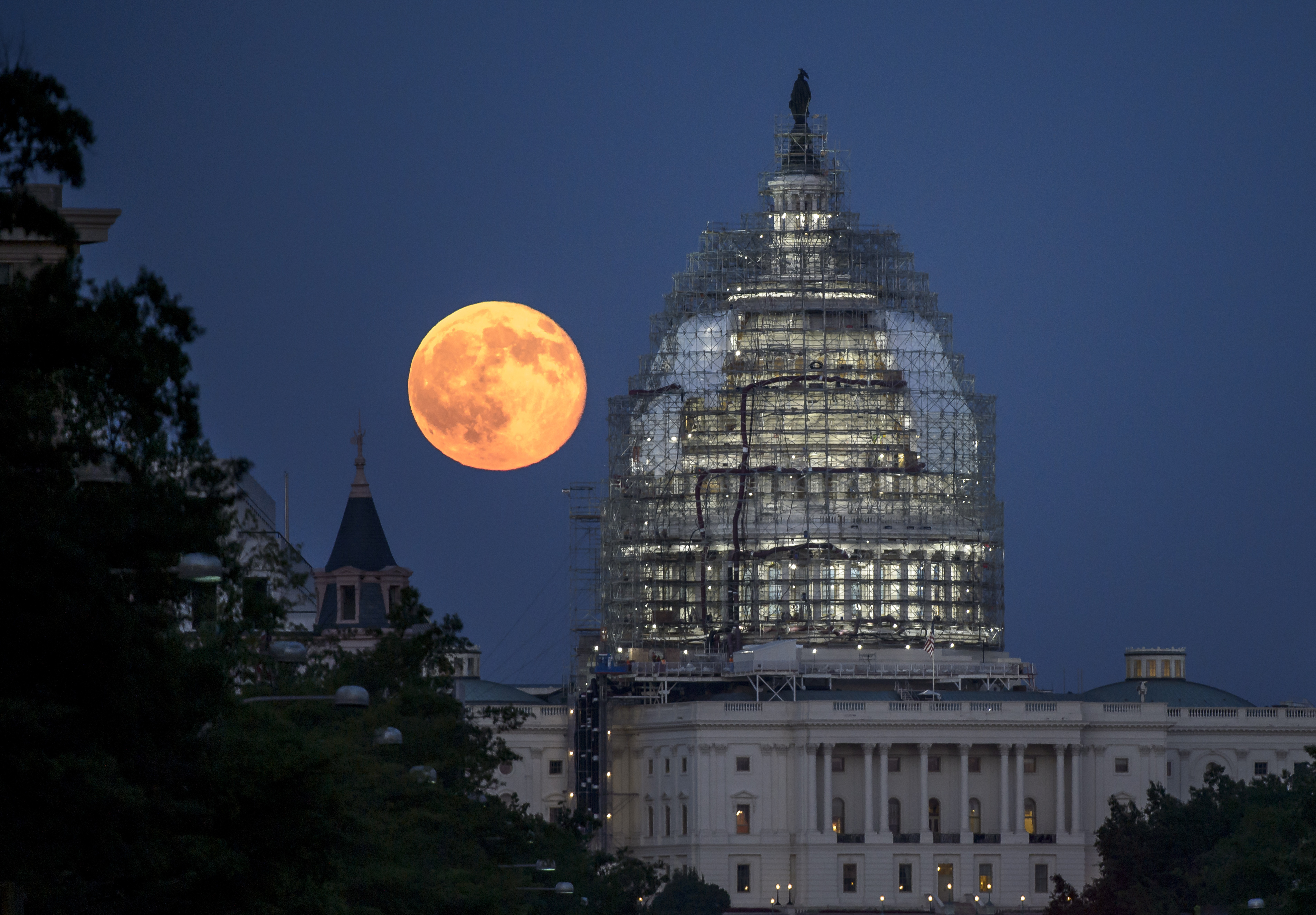 A second full moon for the month of July is seen next to the dome of the U.S. Capitol on Friday, July 31, 2015 in Washington. In recent years, people have been using the name Blue Moon for the second of two full moons in a single calendar month. An older definition of Blue Moon is that it's the third of four full moons in a single season. Photo Credit: (NASA/Bill Ingalls)