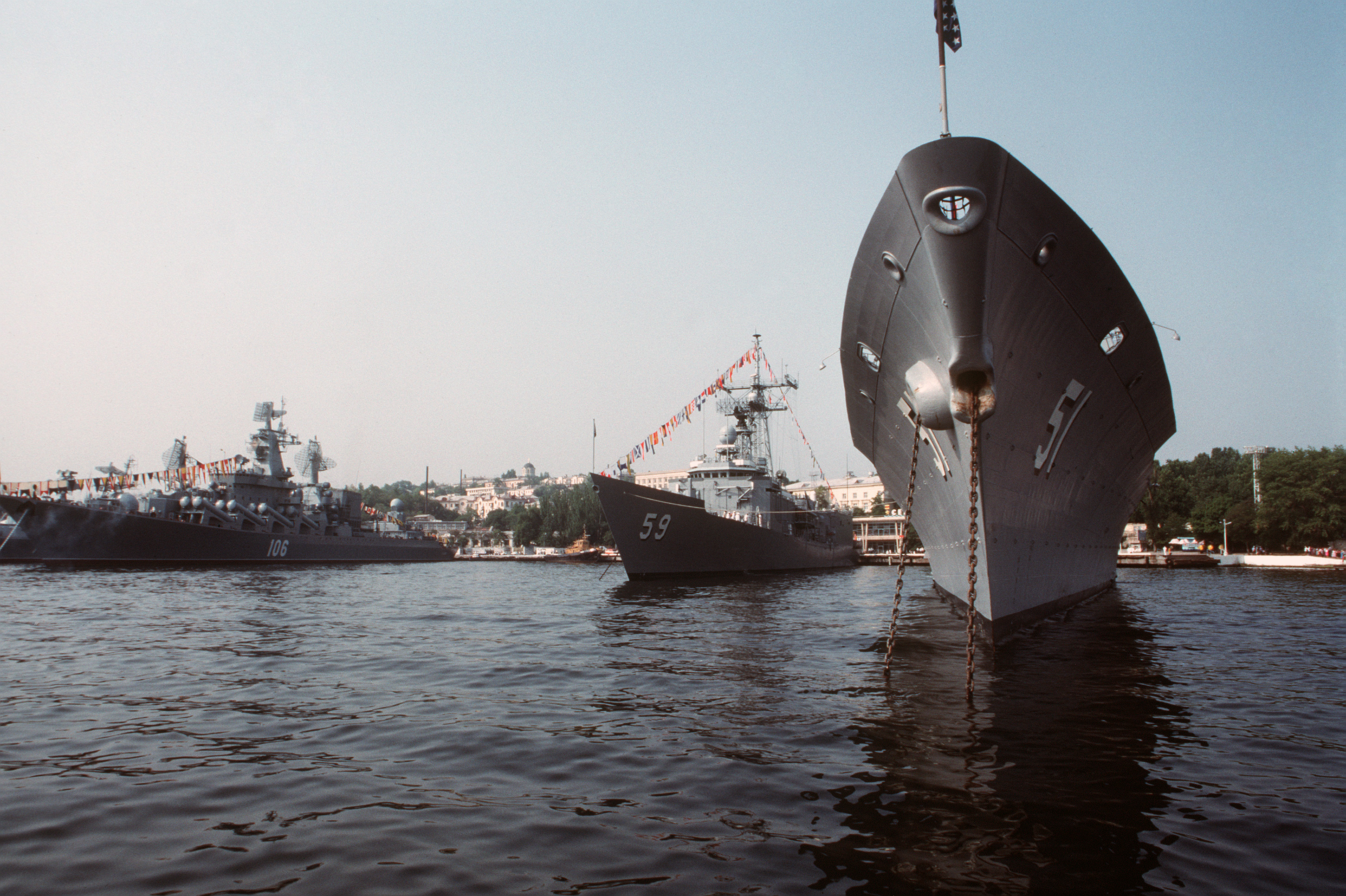 The Aegis guided missile cruiser USS THOMAS S. GATES (CG-51) and the guided missile frigate USS KAUFFMAN (FFG-59) ride at anchor in the harbor. To their left is the Soviet guided missile cruiser Slava in 1989. US Navy Photo
