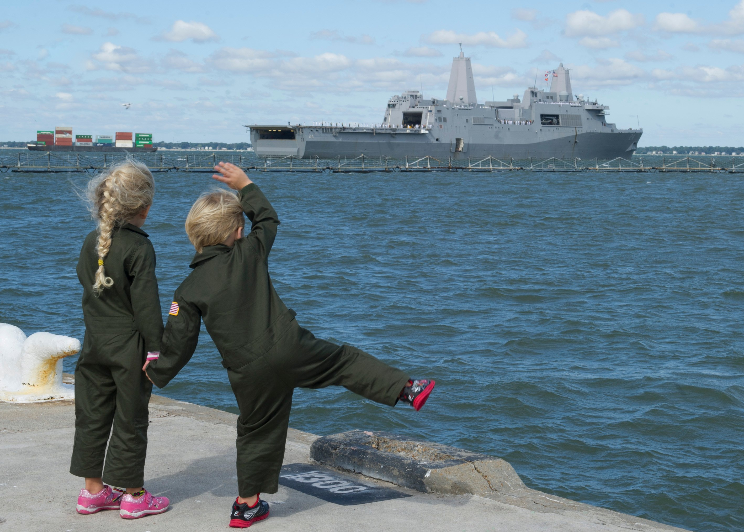 Children wave goodbye to their father, Lt. Chris Robinson, deploying aboard the amphibious transport dock USS Arlington (LPD 24). Arlington deployed as part of the Kearsarge Amphibious Ready Group on Oct. 6, 2015. US Navy photo.