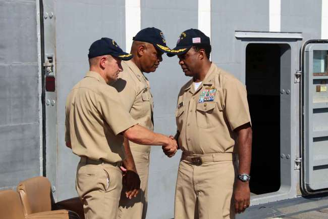 Capt. Steve Shinego, left, shakes hands with Capt. Wesley Smith after he is relieved of command during a change of command ceremony on the ship on Oct. 4, 2013. US Navy photo.