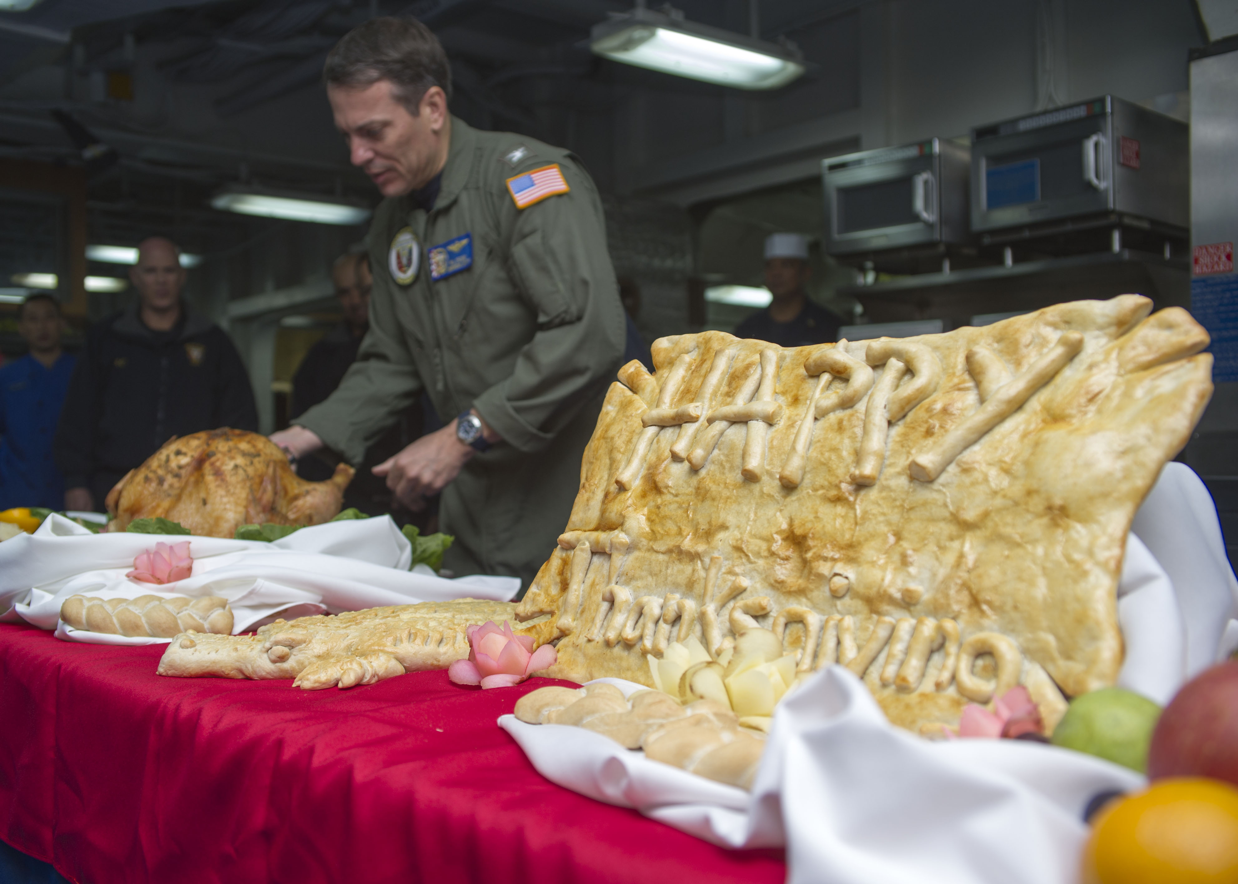 141127-N-LQ926-008 SASEBO, Japan (Nov. 27, 2014) Capt. Paul C. Spedero, commanding officer of the amphibious assault ship USS Peleliu (LHA 5), carves a Thanksgiving turkey before the meal on the mess decks of Peleliu. Peleliu is on its final western Pacific deployment in the U.S. 7th Fleet area of responsibility supporting security and stability in the Indo-Asia-Pacific region before decommissioning early next year. (U.S. Navy photo by Mass Communication Specialist 2nd Class Alex Van'tLeven/Released)