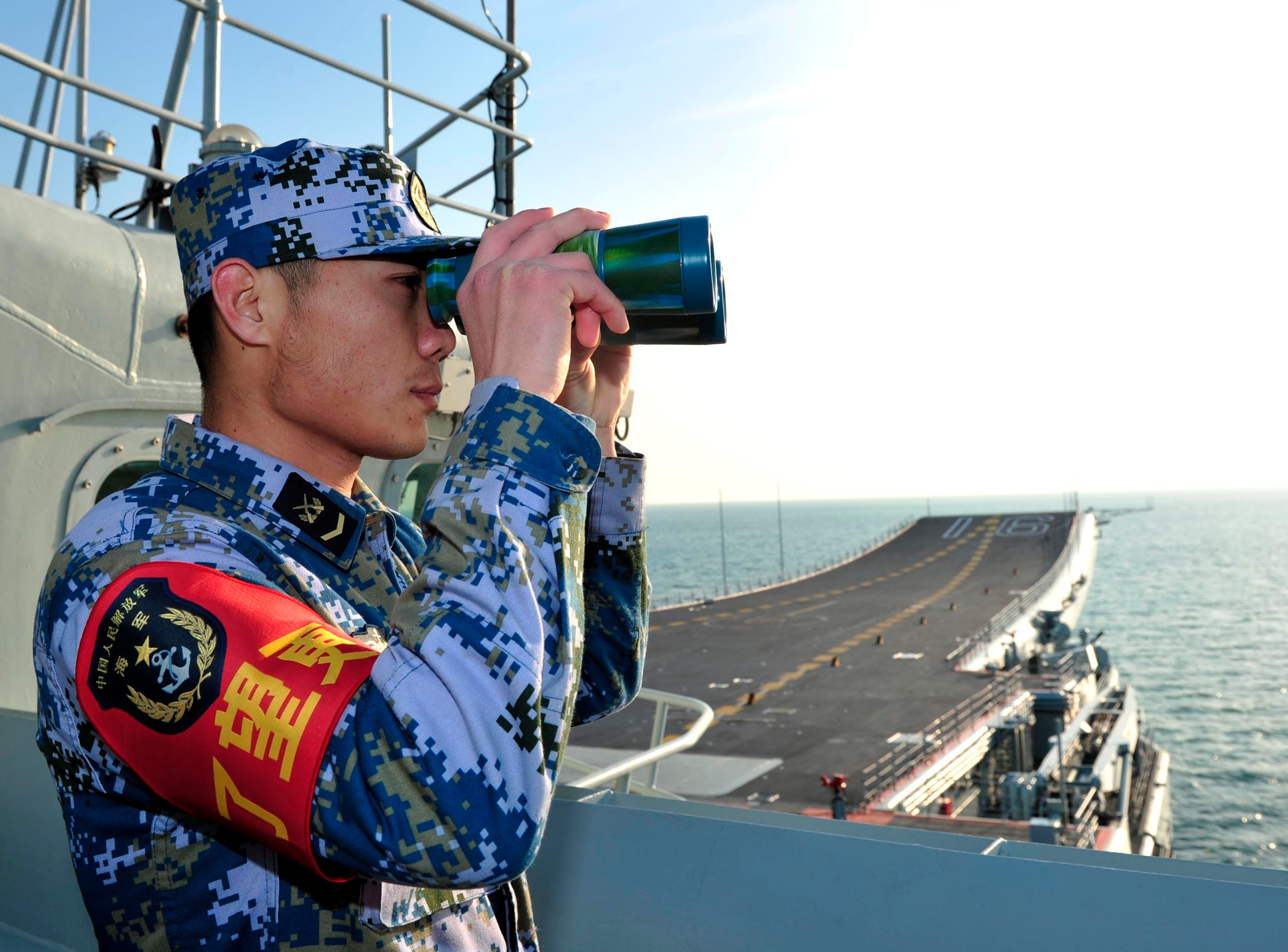 A naval soldier of the Chinese People's Liberation Army (PLA) views through a pair of binoculars onboard China's first aircraft carrier Liaoning as it visits a military harbour on the South China Sea. Xinhua Photo