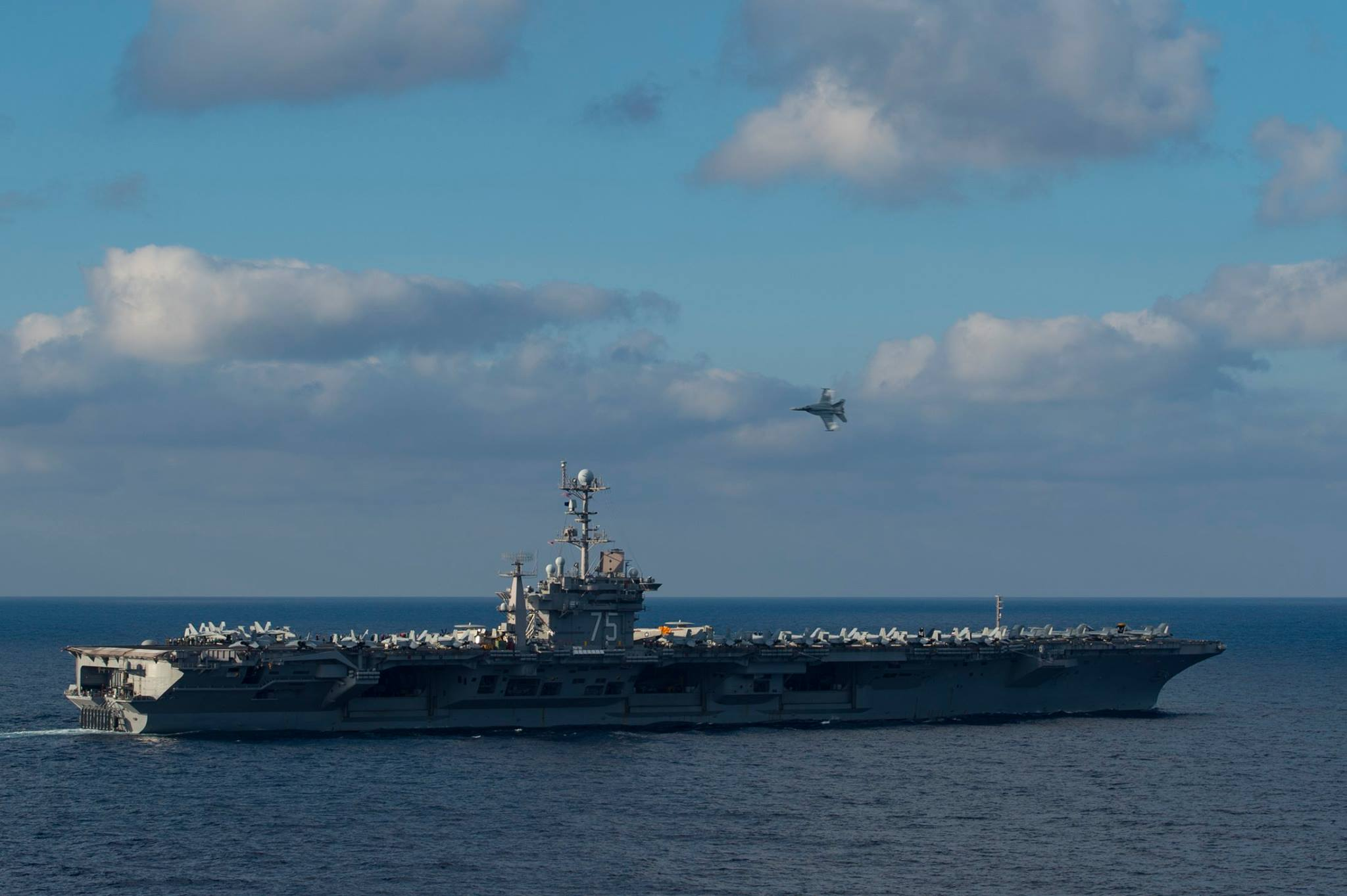 An F/A-18E Super Hornet assigned to the Pukin' Dogs of Strike Fighter Squadron (VFA) 143 begins a supersonic flyby over the flight deck of the aircraft carrier USS Harry S. Truman (CVN-75) on Dec. 3, 2015. US Navy Photo
