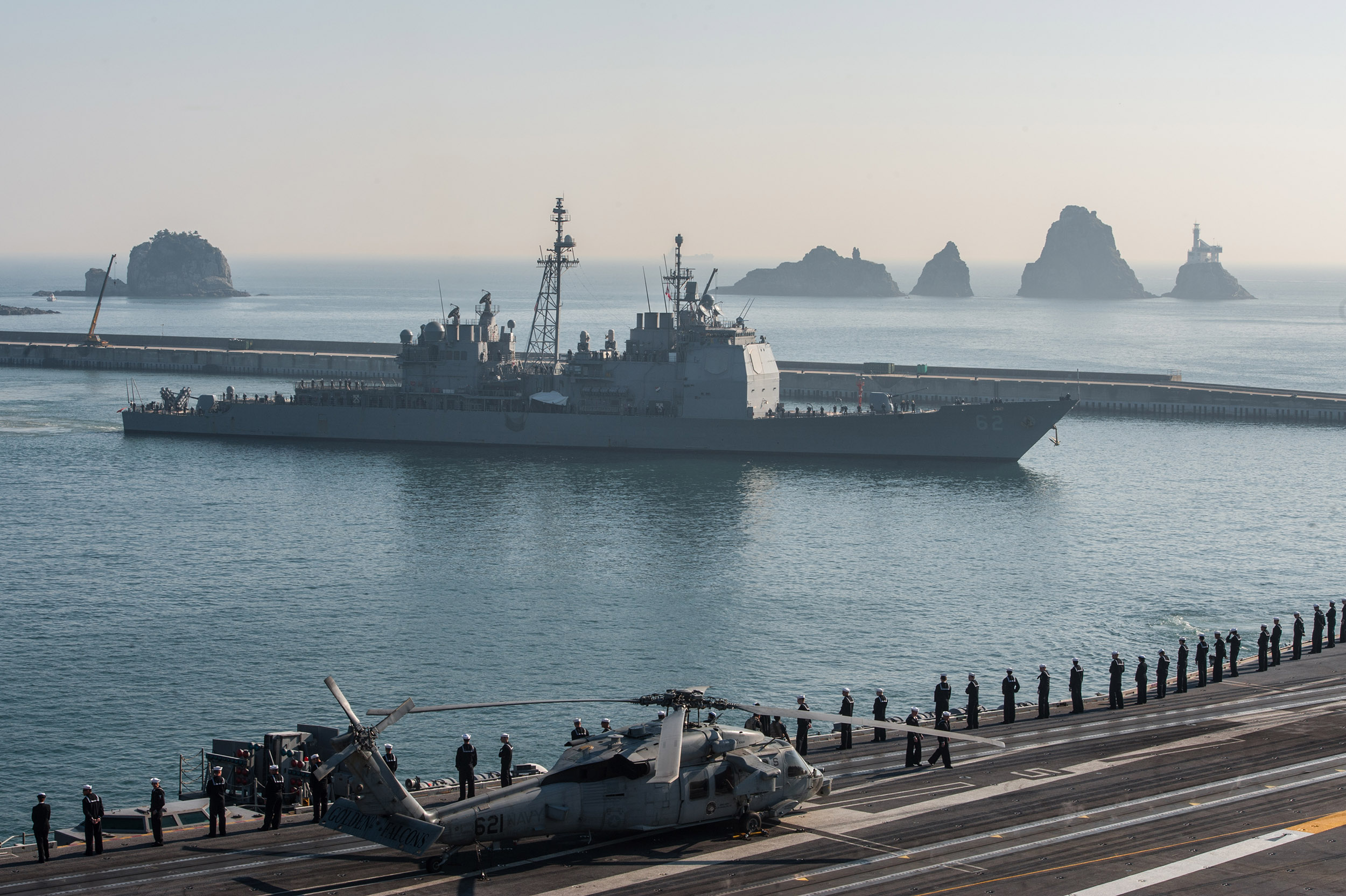 Sailors man the rails as the U.S. Navy's only forward-deployed aircraft carrier USS Ronald Reagan (CVN 76) and the Ticonderoga-class guided-missile cruiser USS Chancellorsville (CG 52) depart Busan in 2014. US Navy Photo