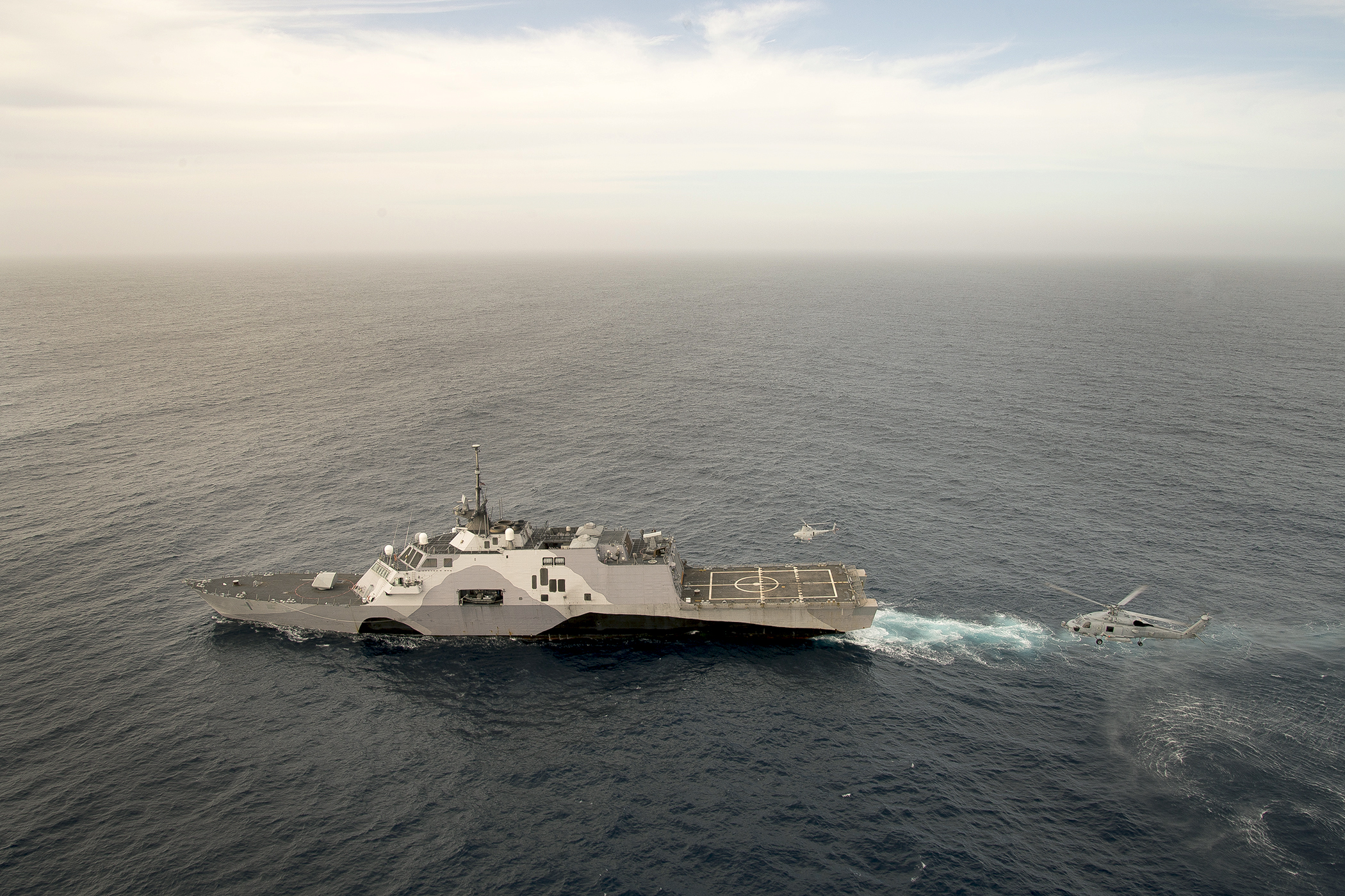 An MH-60R Sea Hawk helicopter and an MQ-8B Fire Scout unmanned aerial vehicle conduct coordinated flight operations with the littoral combat ship USS Freedom (LCS-1) in the Southern California operating area on April 30, 2015. US Navy photo.