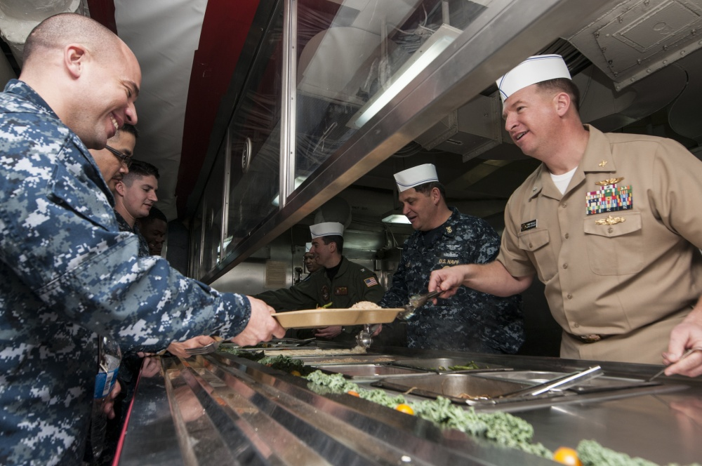 Cmdr. Thomas Neville, supply officer of Nimitz-class aircraft carrier USS Abraham Lincoln (CVN-72), Capt. Ronald Ravelo, Lincoln's commanding officer, Capt. Todd Marzano, Lincoln's executive officer, and Master Chief Lee Salas, Lincoln's command master chief, help serve food to Sailors during the first meal on the mess decks as part of the first phase of the crew move aboard process. US Navy Photo