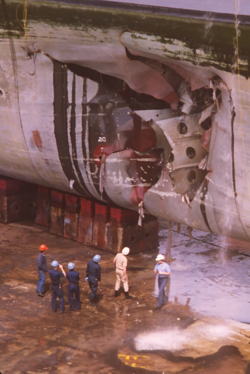 Officials survey the damage of USS Tripoli while the ship was in drydock in Bahrain following a mine attack. US Navy Photo
