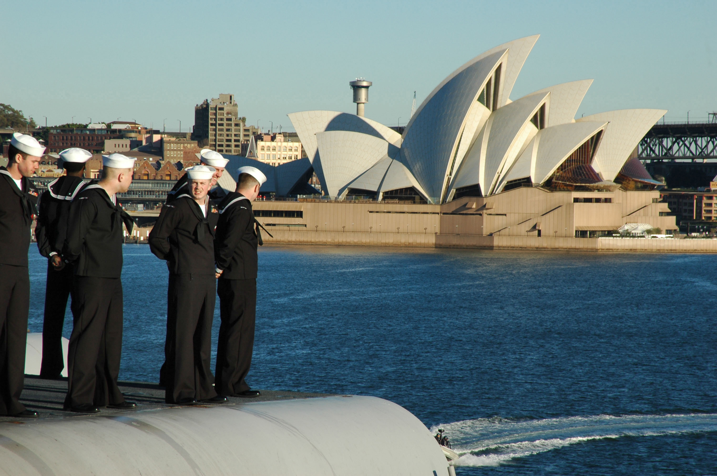 U.S. sailors man the rails aboard USS Kitty Hawk (CV-63) sails the Sydney Opera House while pulling into Sydney, Australia in 2005. US Navy Photo