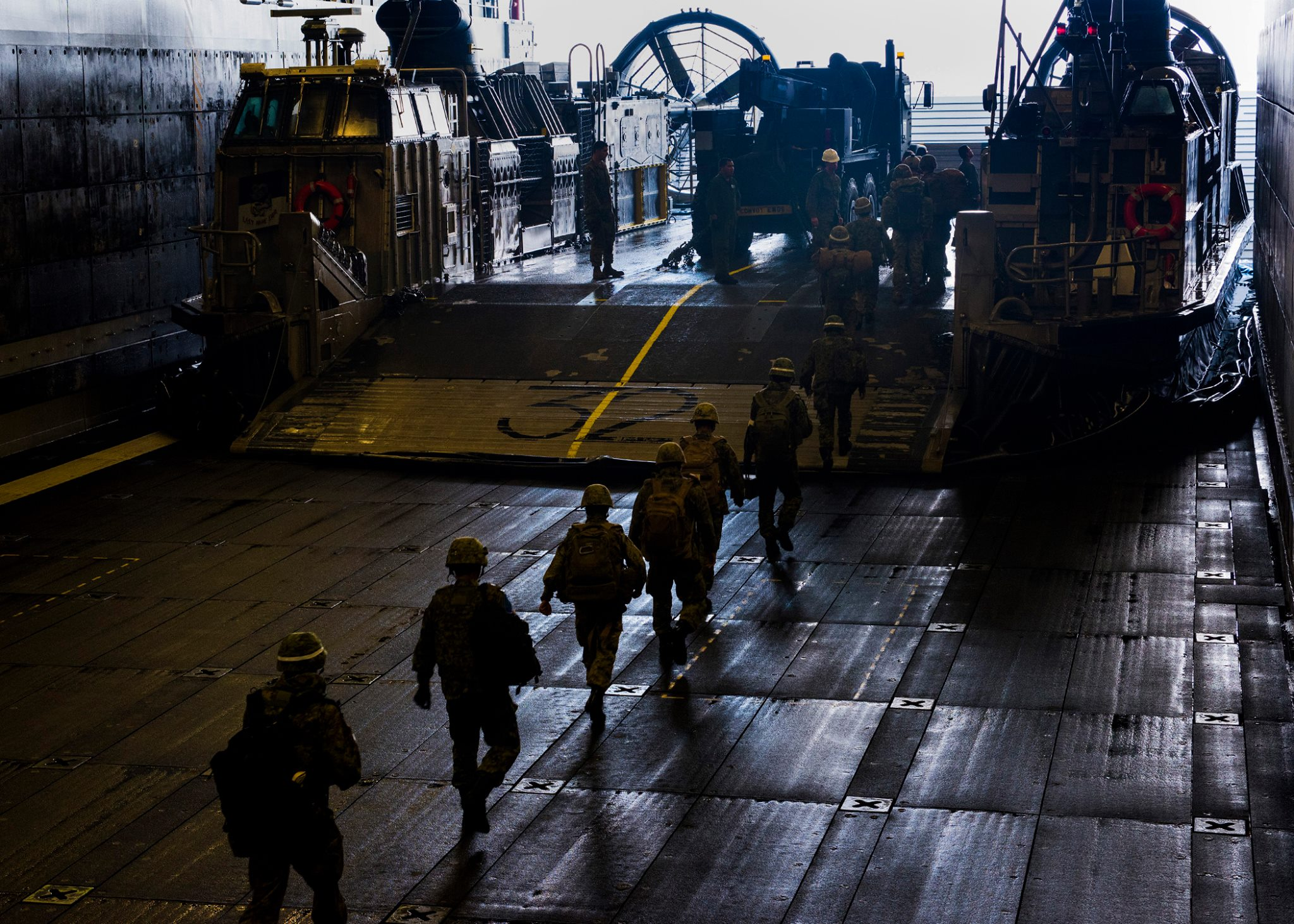 Japanese Self Defense Force soldiers board a Landing Craft Air Cushion (LCAC) in the well deck of USS Somerset (LPD-25). US Marine Corps Photo