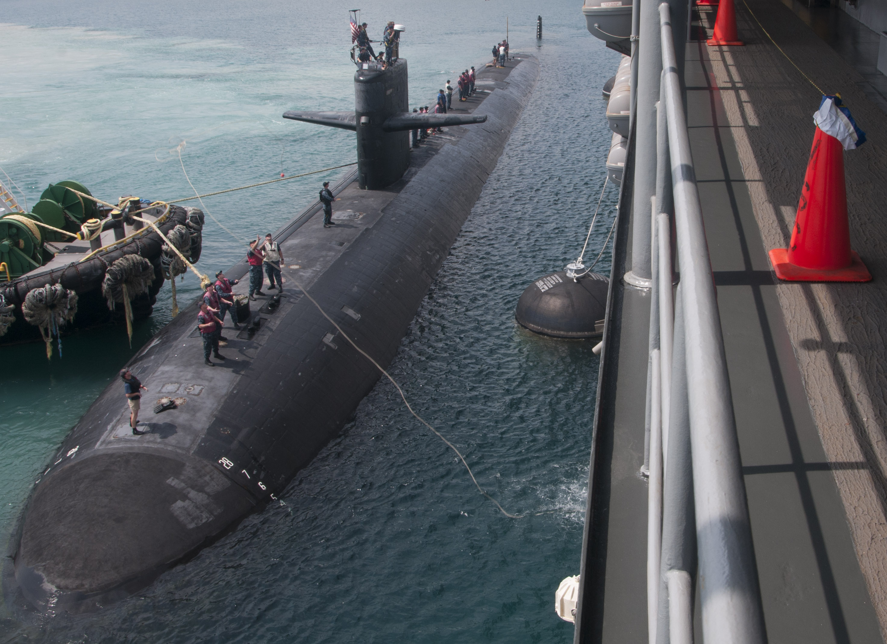 The Los Angeles-class attack submarine USS City of Corpus Christi (SSN 705) maneuvers into position to moor alongside the submarine tender USS Emory S. Land (AS 39) to complete repair maintenance actions in Guam in September 2015. US Navy photo.