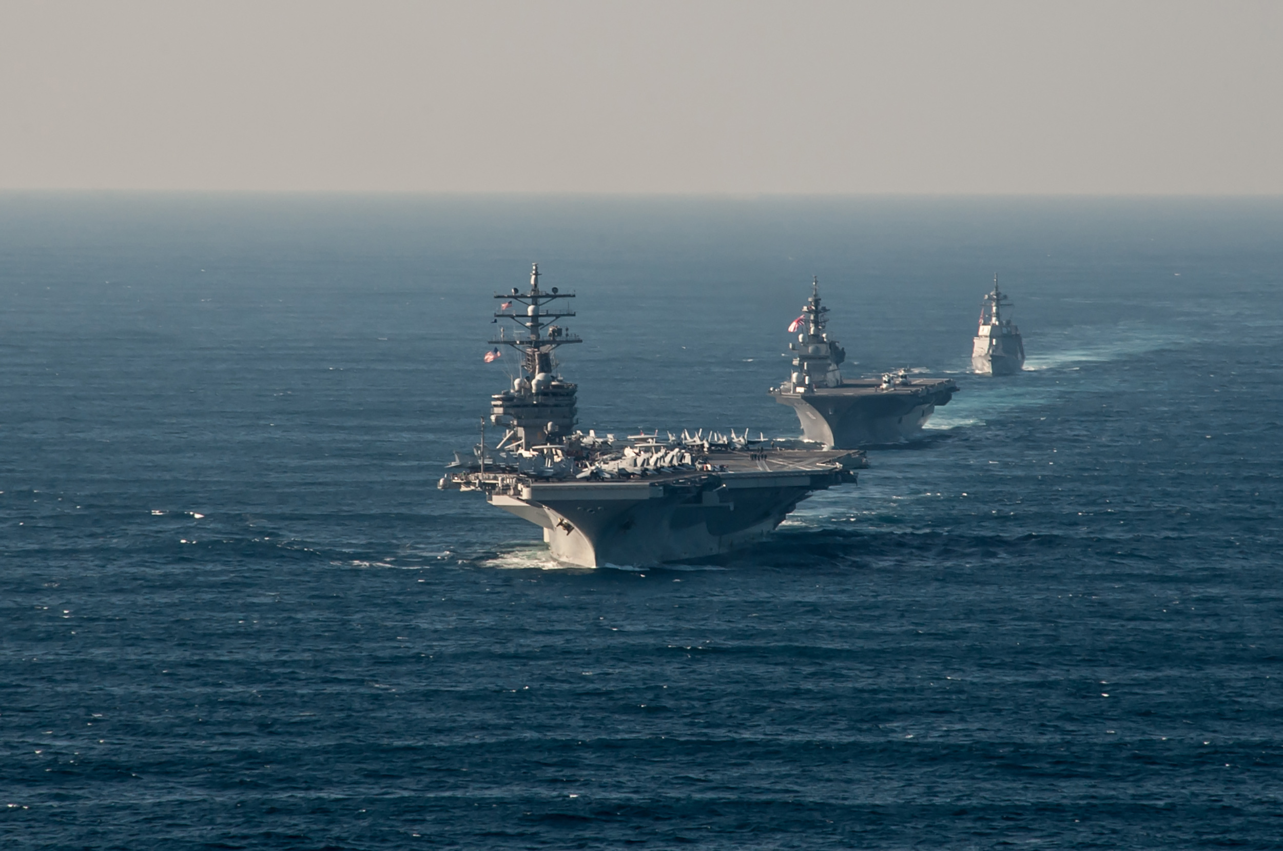 USS Ronald Reagan (CVN-76) transits alongside Japan Maritime Self-Defense Force (JMSDF) Izumo-class helicopter destroyer JS Izumo (DDH 183) and JMSDF Akizuki-class destroyer JS Teruzuki (DD 116) on Oct. 18, 2015. US Navy Photo