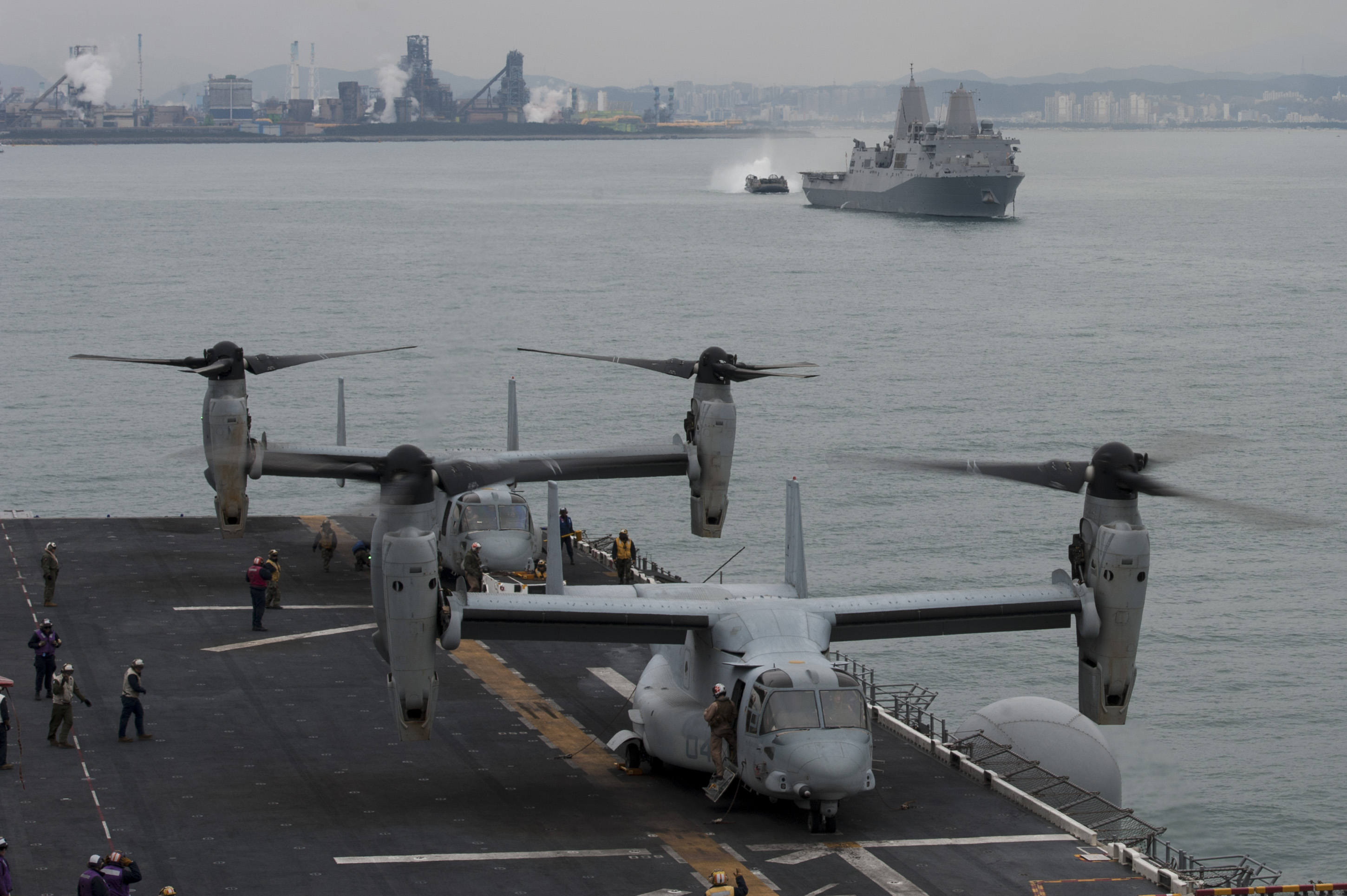 MV-22 Osprey tilt rotor aircraft prepare to take off from the flight deck of the amphibious assault ship USS Bonhomme Richard (LHD 6), while in the background an landing craft air cushion (LCAC) approaches the amphibious transport dock ship USS Green Bay (LPD 20) in April 2015. US Navy photo.