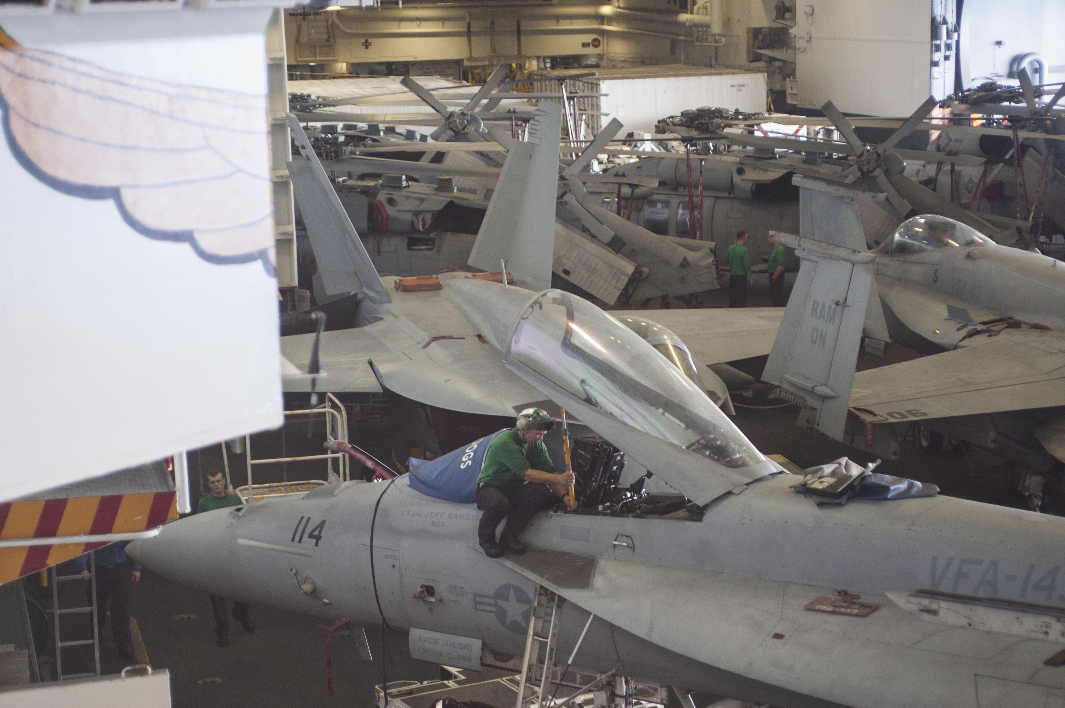 Aviation Structural Mechanic (Equipment) 2nd Class M. V. Volosko, assigned to the Pukin Dogs of Strike Fighter Squadron (VFA) 143, places a canopy brace on an F/A-18E Super Hornet in the hangar bay of the aircraft carrier USS Harry S. Truman (CVN 75) on June 17, 2015. US Navy photo.