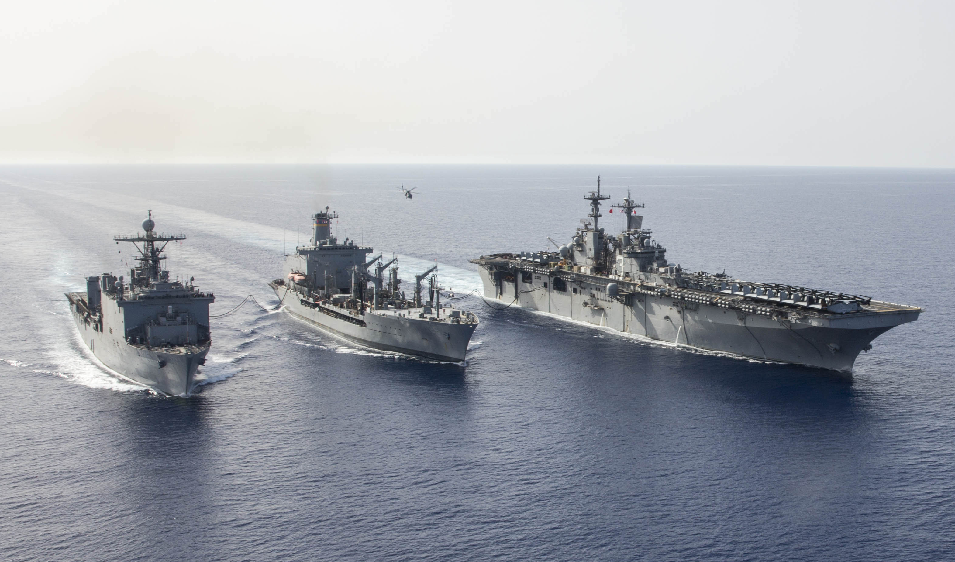 USS Kearsarge (LHD-3) (right) and the amphibious dock landing ship USS Oak Hill (LSD-51) (left) transit alongside the Military Sealift Command fleet replenishment oiler USNS Kanawha (T-AO-196) on April 7, 2016. US Navy Photo