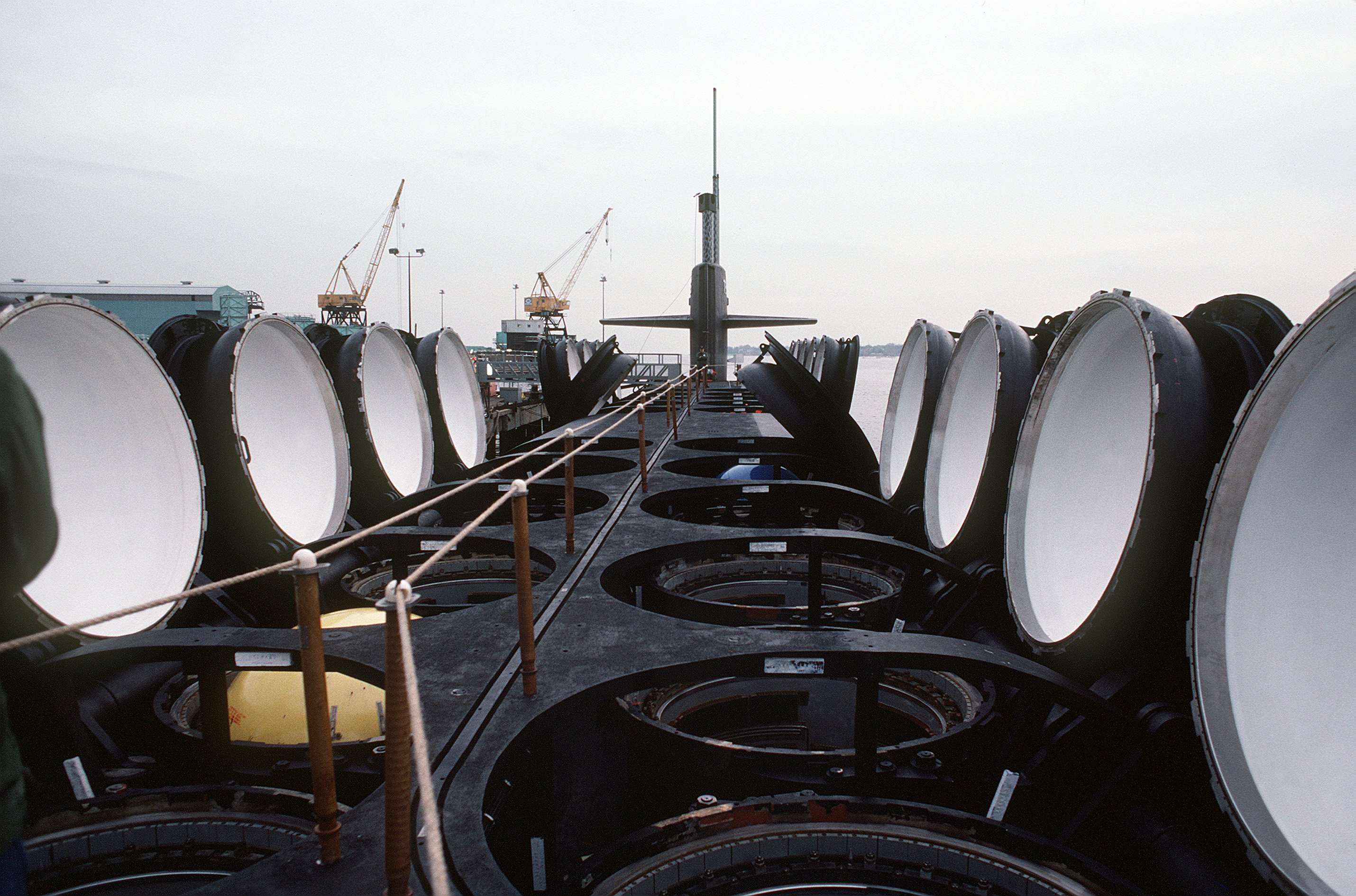 A deck view, looking toward the bow, of the nuclear-powered ballistic missile submarine OHIO (SSBN-726) with its missile tubes opened during precommissioning activities. The submarine, built by General Dynamics Corp., carries Trident C-4 (UGM-96) submarine-launched ballistic missiles.