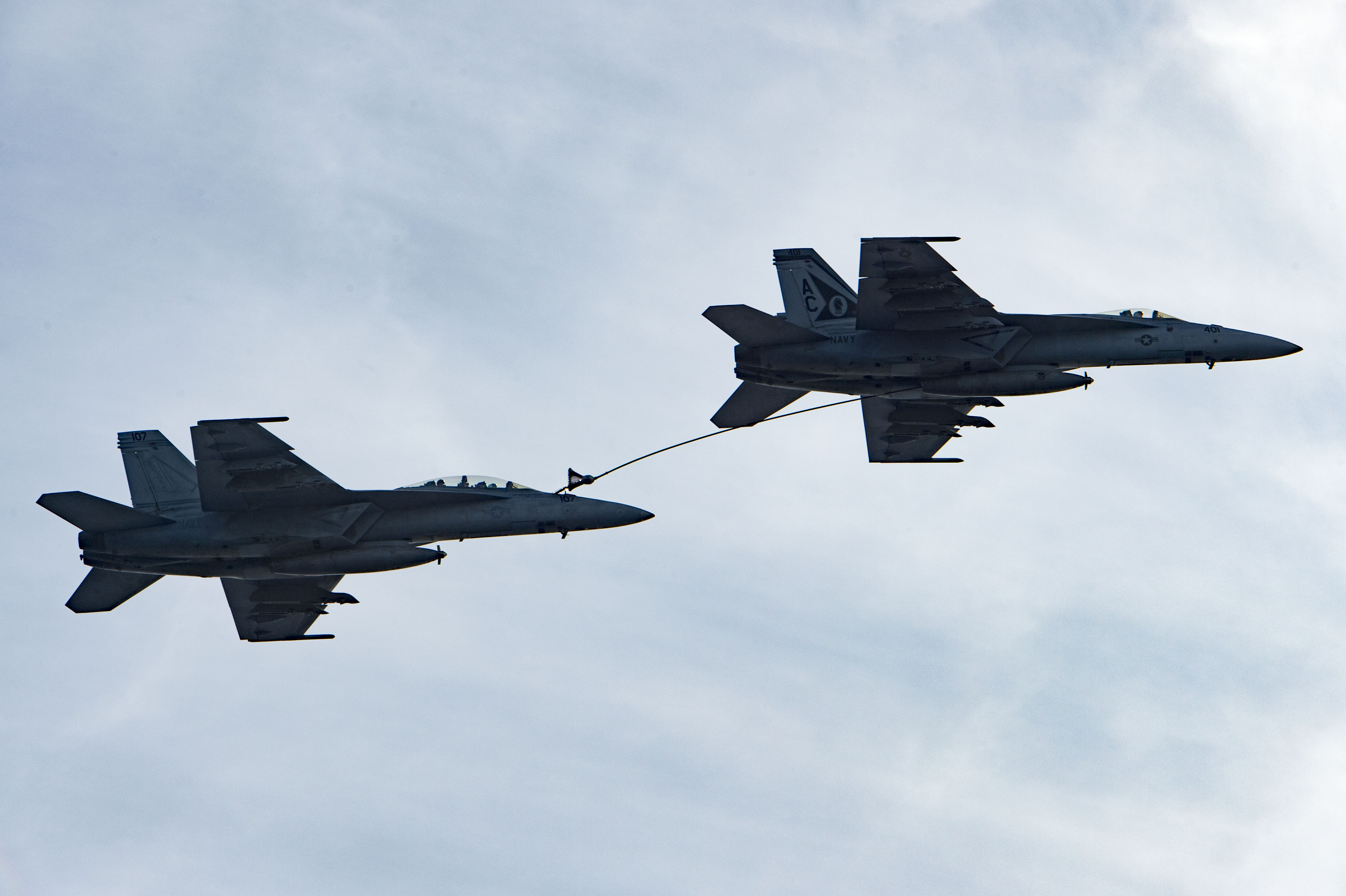 An F/A-18F Super Hornet assigned to the Fighting Swordsmen of Strike Fighter Squadron (VFA) 32 (left) receives fuel from an F/A-18E Super Hornet assigned to the Gunslingers of Strike Fighter Squadron (VFA) 105 on April 19, 2016. US Navy photo.