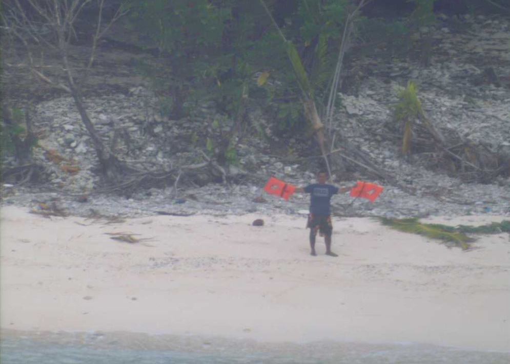One of three men discovered by a U.S. Navy P-8A Poseidon maritime surveillance aircraft after their 19-foot skiff capsized after setting out to sea from Pulap, FSM, three days earlier, waves lifejackets to attract attention on the uninhabited island of Fanadik. US Navy photo.