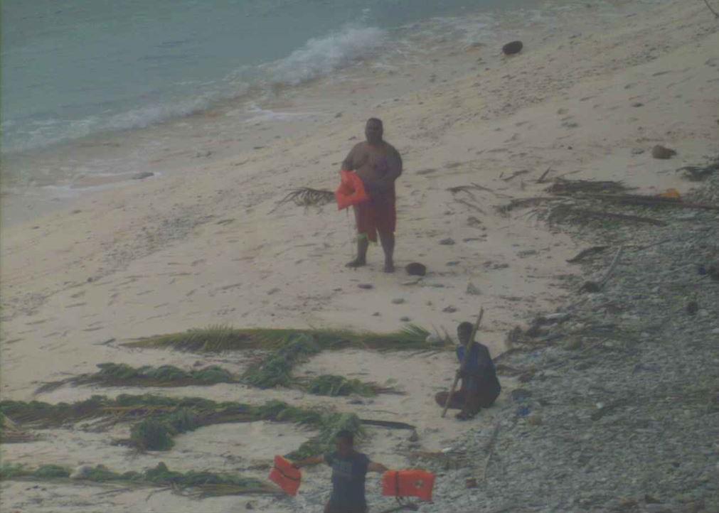 Three men wave life jackets and look on as a U.S. Navy P-8A Poseidon maritime surveillance aircraft discovers them on the uninhabited island of Fanadik.US Navy photo.