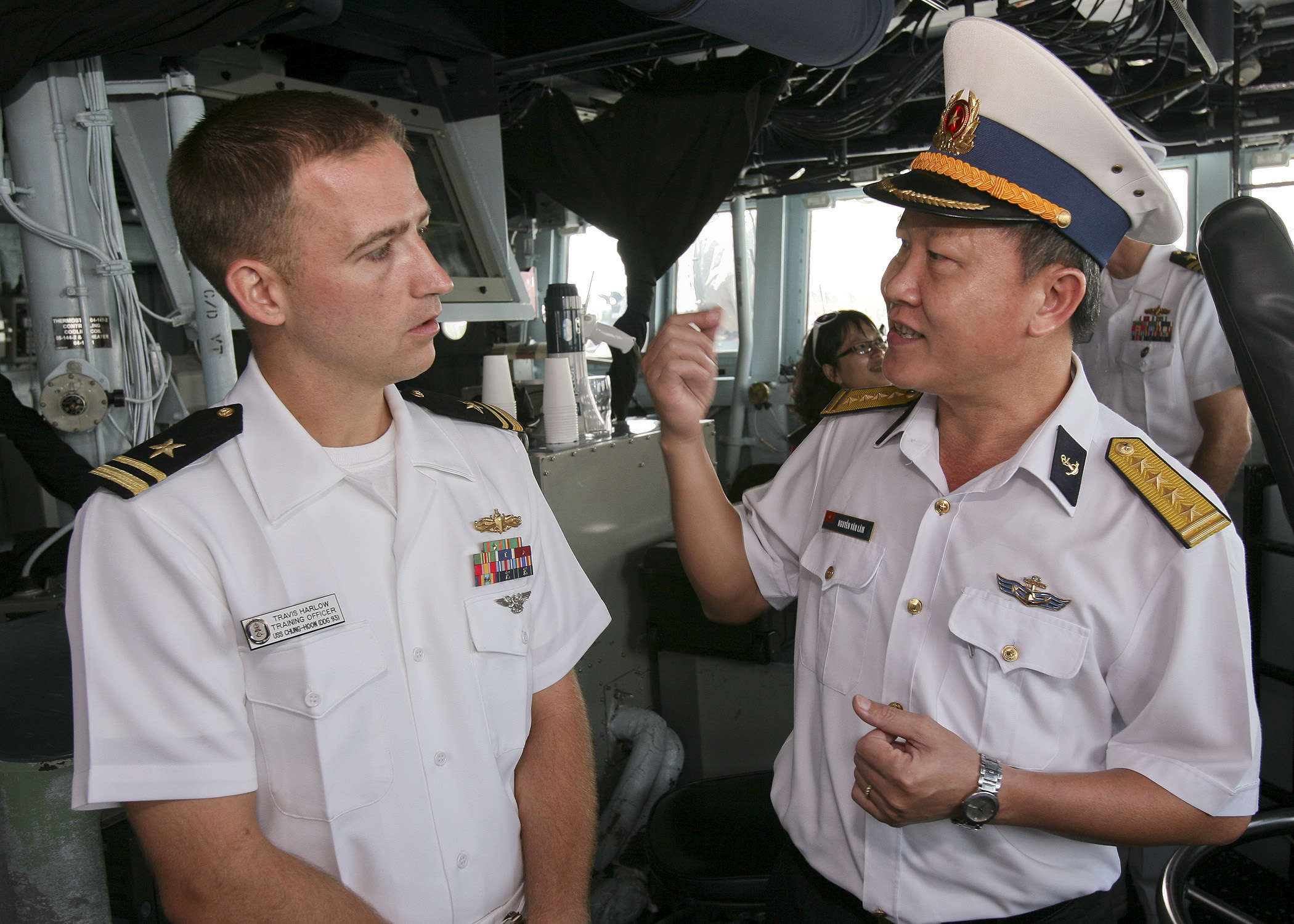 Lt. (jg) Travis Harlow, training officer aboard the guided-missile destroyer USS Chung-Hoon (DDG-93), explains his job responsibilities to senior leaders from the Vietnam People's Navy in 2013. US Navy Photo