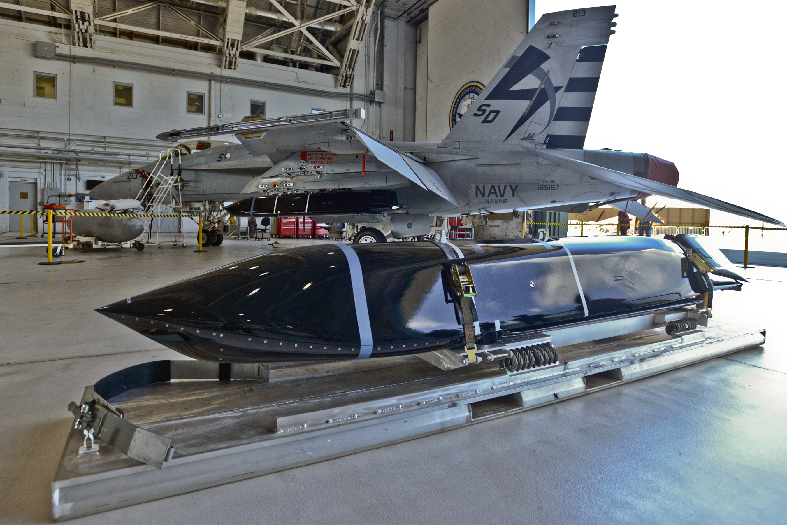 A LRASM missile in a hangar with a F/A-18E Super Hornet. Lockheed Martin Photo
