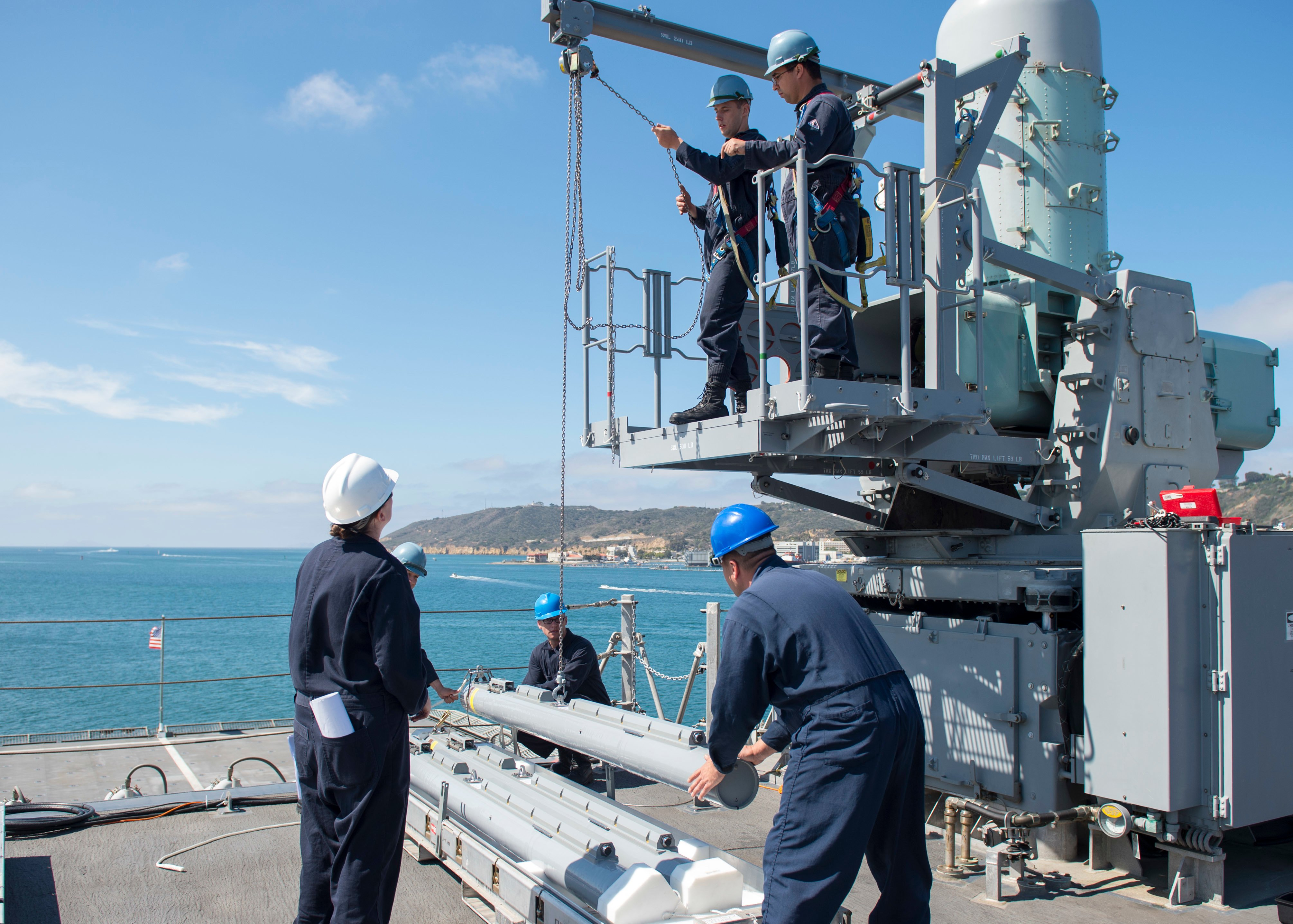 Sailors assigned to the littoral combat ship USS Coronado (LCS 4) load a rolling-airframe-missile launcher onto the ship on August 12, 2015. US Navy photo.