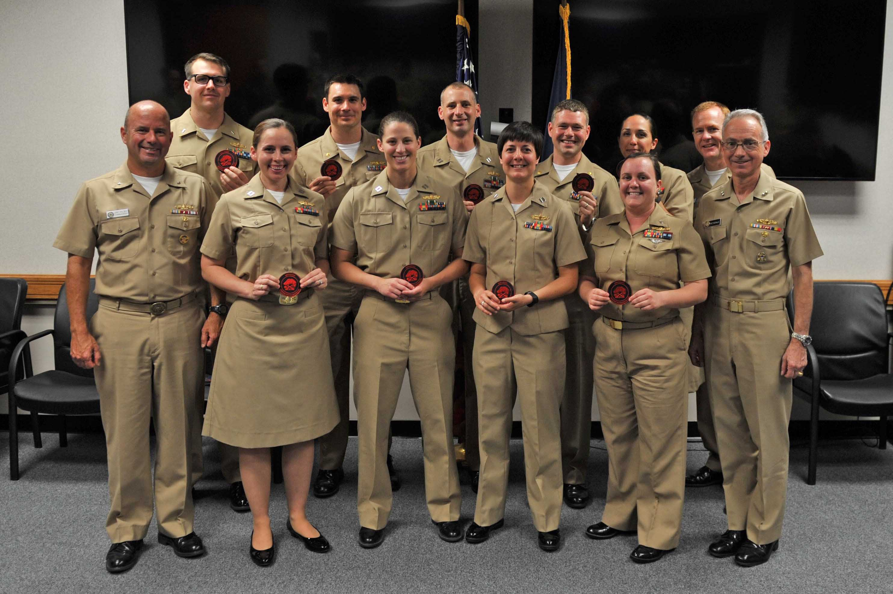 Rear Adm. Jim Kilby, commander of Naval Surface and Mine Warfighting Development Center (SMWDC), congratulates graduates of the first Amphibious Warfare Tactics Instructor course. US Navy photo.
