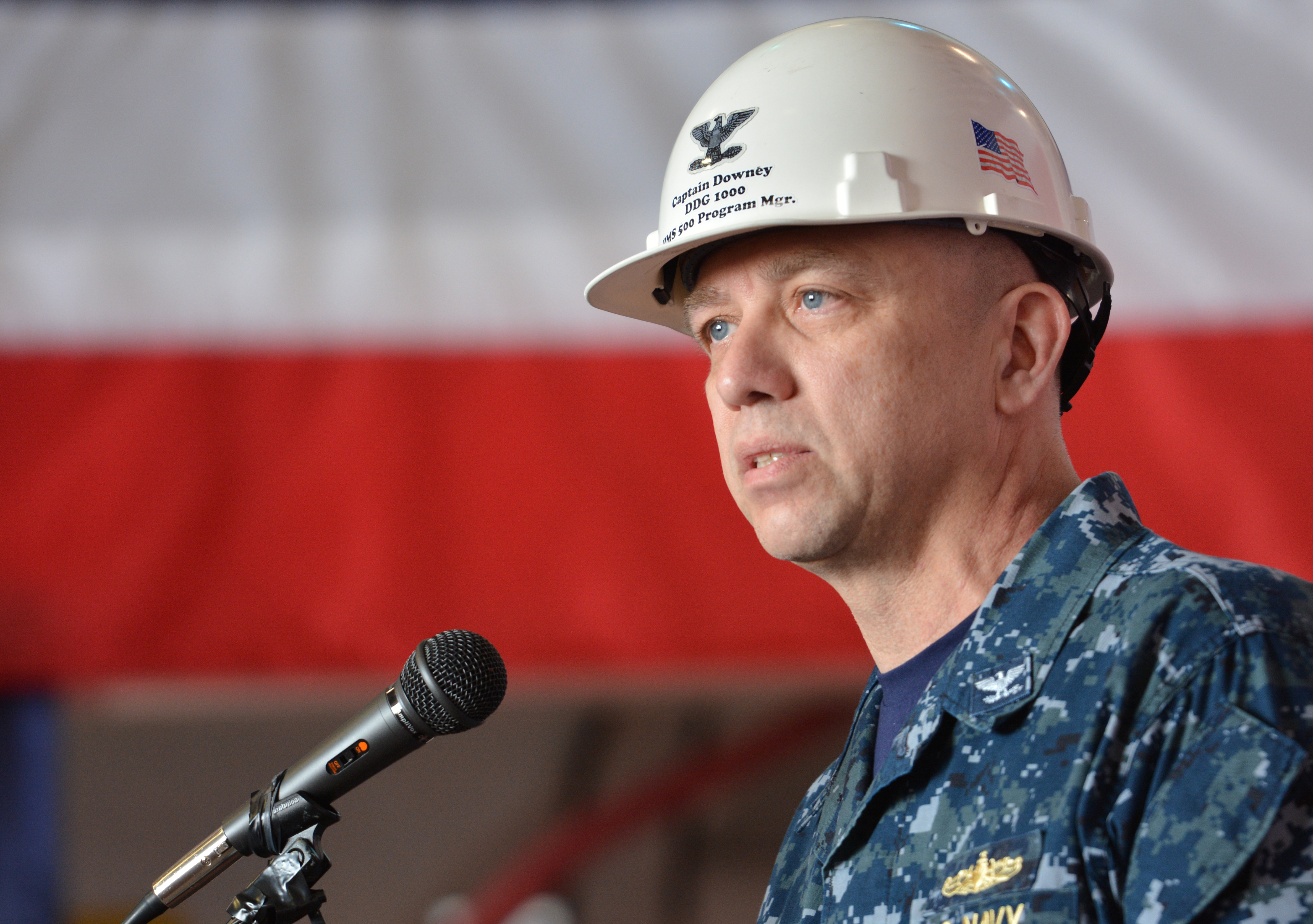 Capt. James Downey, then-DDG 1000 program manager, speaks to assembled crew and guests in the hangar bay aboard the future guided-missile destroyer USS Zumwalt (DDG 1000) following a transfer of ownership ceremony on May 20, 2016. US Navy photo.