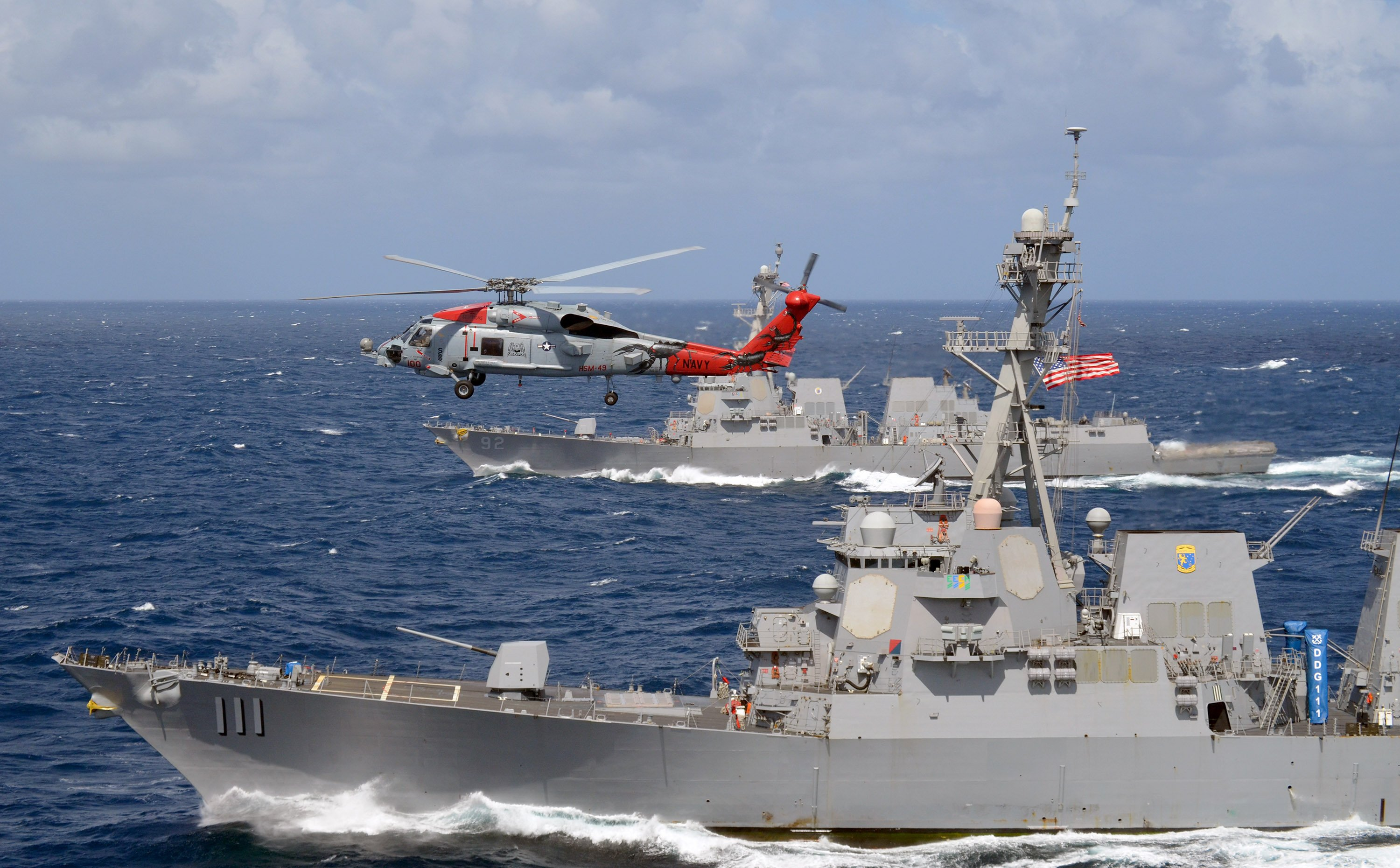 "An MH-60R Seahawk, attached to the ""Warbirds"" of Helicopter Maritime Strike Squadron (HSM) 49, flies over the guided-missile destroyers USS Spruance (DDG 111) and USS Momsen (DDG 92), two of the three guided-missile destroyers deployed in a U.S. 3rd Fleet Pacific Surface Action Group (PAC SAG). US Navy photo."