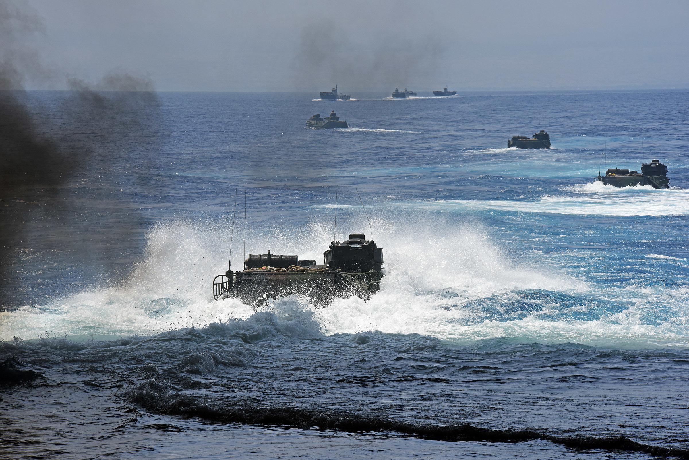 Amphibious assault vehicles depart the well deck of amphibious transport dock ship USS San Diego (LPD 22) while Royal Australian Navy LHD landing craft wait to escort them on July 18, 2016. US Navy photo.