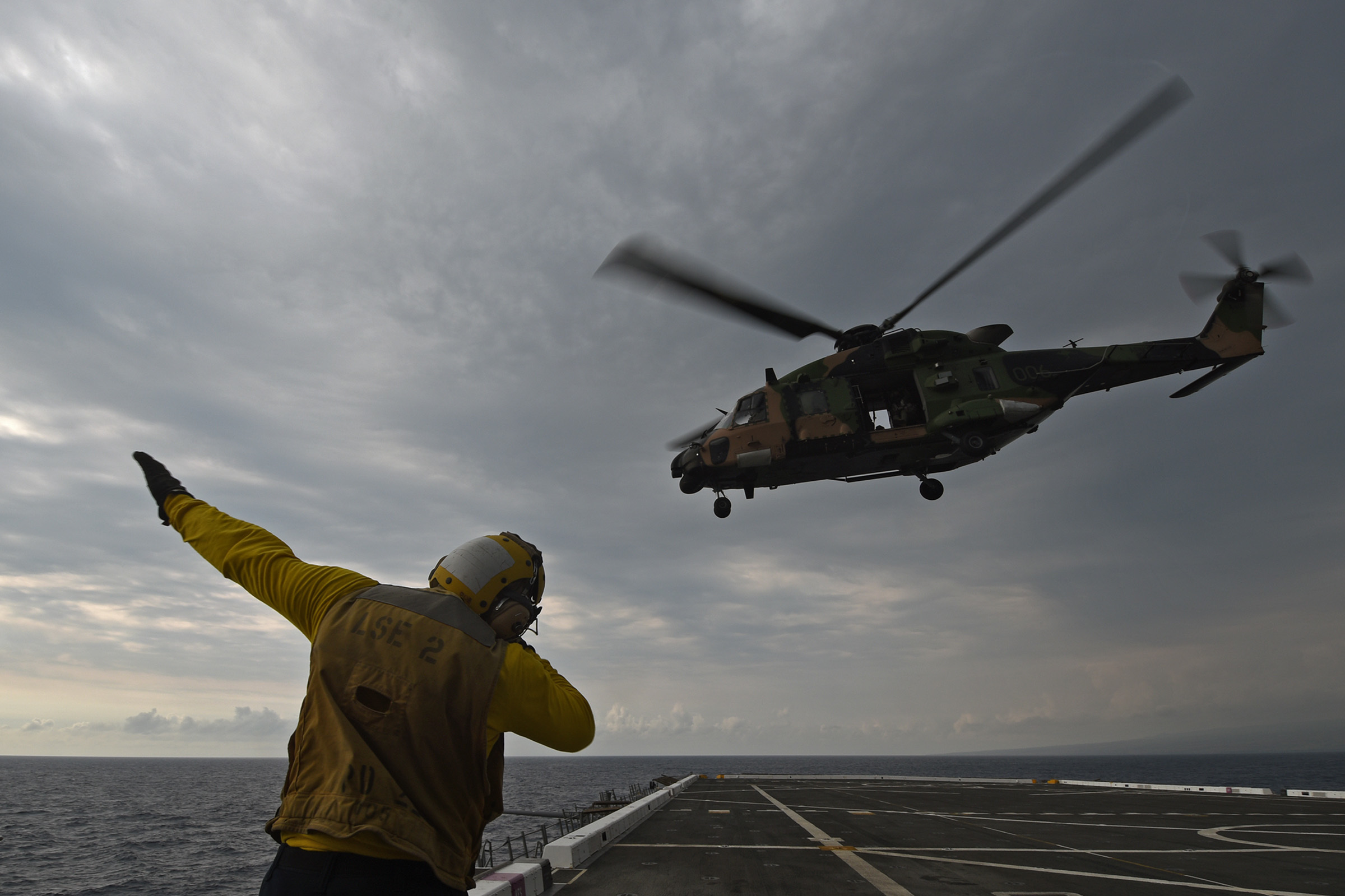 Aviation Boatswain's Mate (handling) Airman Joshua Evans signals a Royal Australian Navy MRH-90 Taipan to enter the pattern above the flight deck of amphibious transport dock ship USS San Diego (LPD 22) during interoperability testing in Rim of the Pacific 2016. US Navy photo.