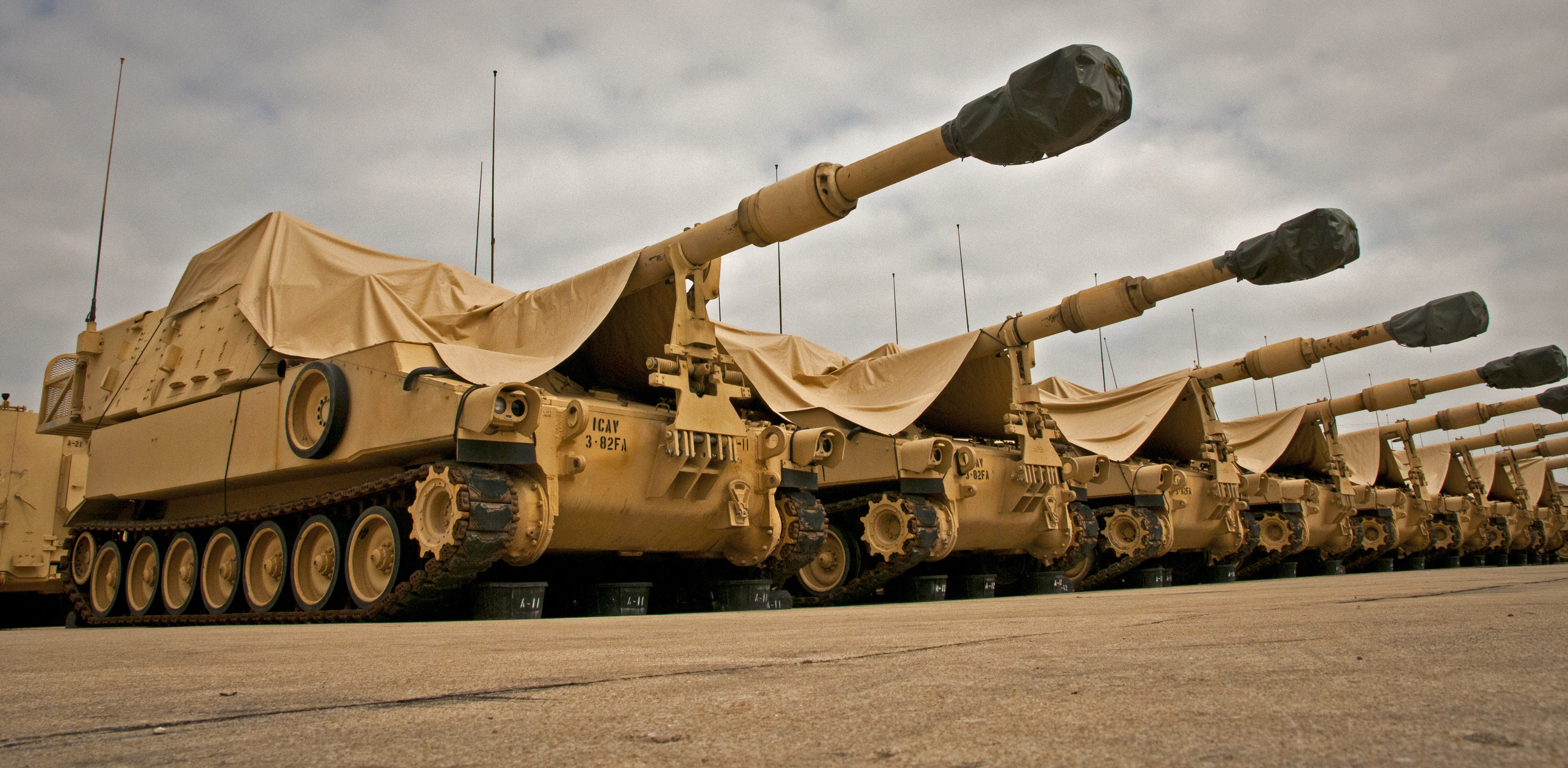 M109A6 Paladin howitzers are seen under a cloudy sky at the 3rd Battalion, 82nd Field Artillery Regiment motor pool at Fort Hood, Texas on March 22, 2013. US Army Photo