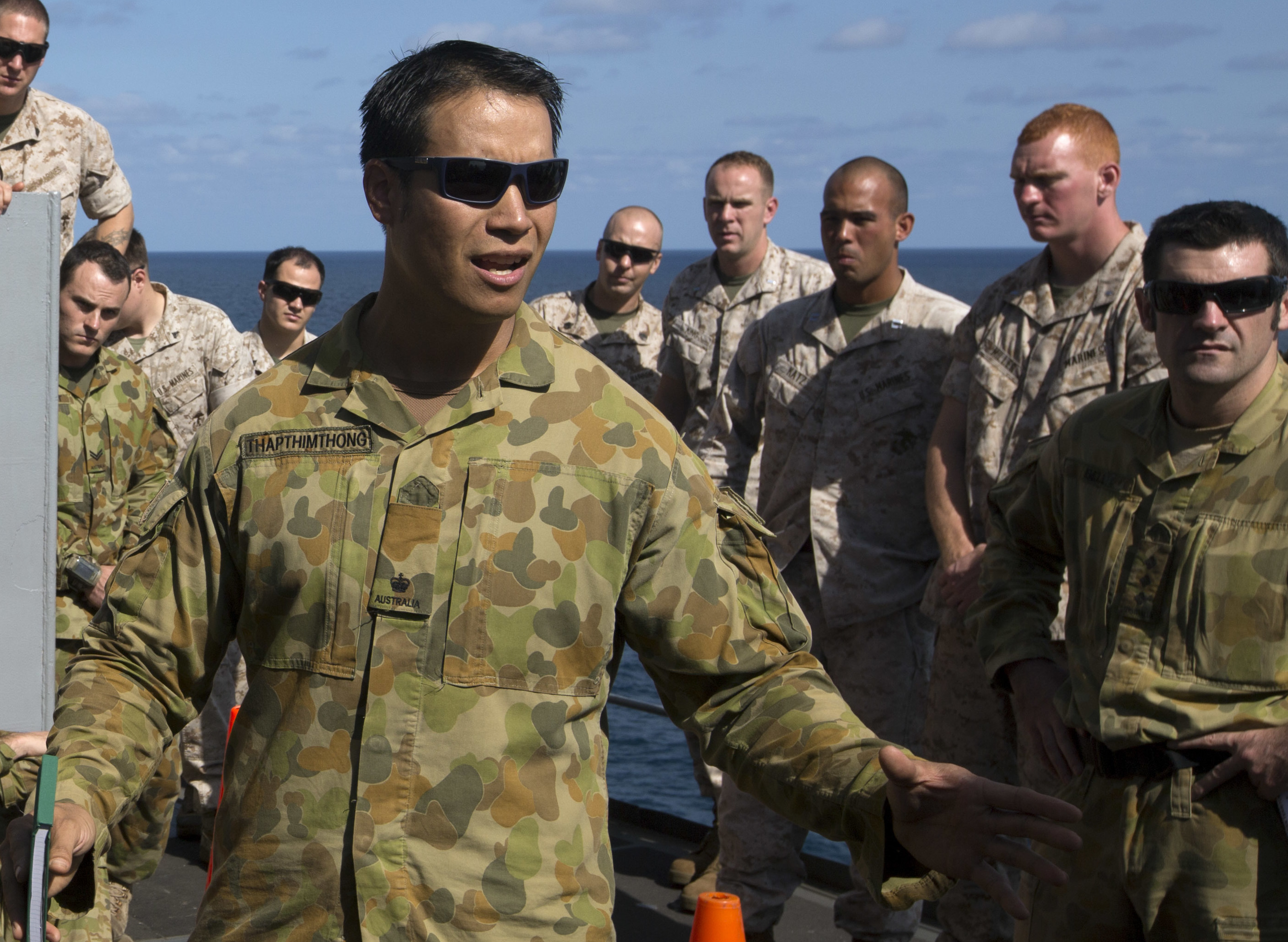 Australian Defense Force Maj. Richard Thapthimthong gives a rehearsal of concept brief to Australian service members and U.S. Marines aboard the USS Ashland (LSD-48) on July 10, 2015. US Marine Corps Photo