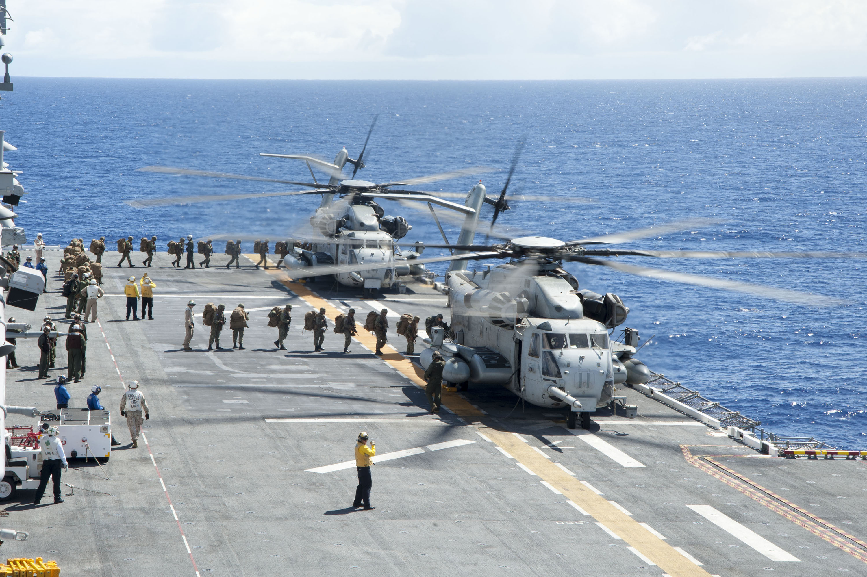 Marines assigned to 2nd Battalion, 3D Marine Regiment board two CH-53 Sea Stallion helicopters on the flight deck of amphibious assault ship USS America (LHA-6) as part of Rim of the Pacific 2016. US Navy photo.