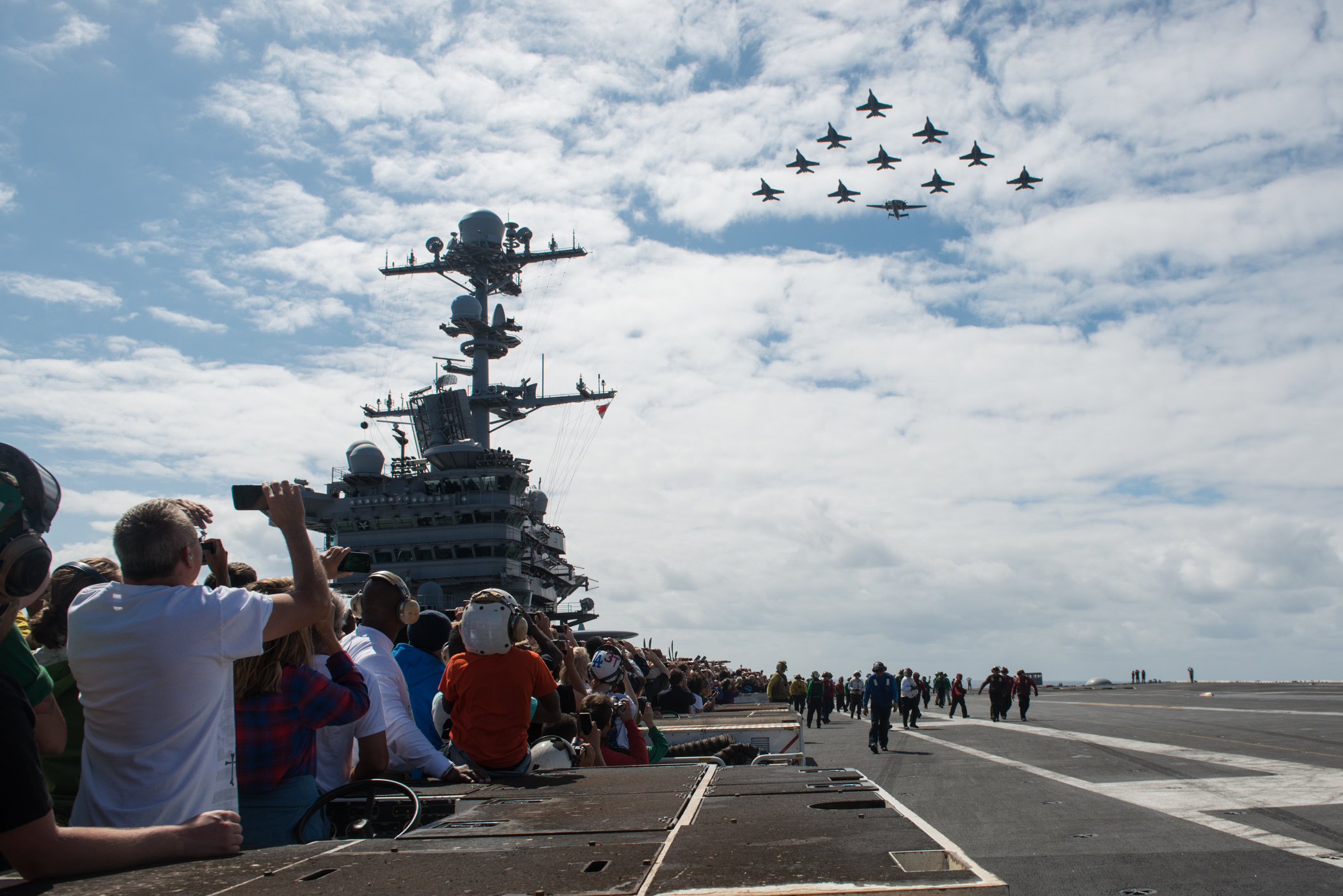 Sailors, family and friends watch as aircraft from Carrier Air Wing (CVW) 9 fly in formation above USS John C. Stennis (CVN 74) during an air power demonstration on Aug. 7, 2016, during the tiger cruise, which is an opportunity for Sailors to invite their family and friends to experience life underway aboard a Navy ship. US Navy photo.