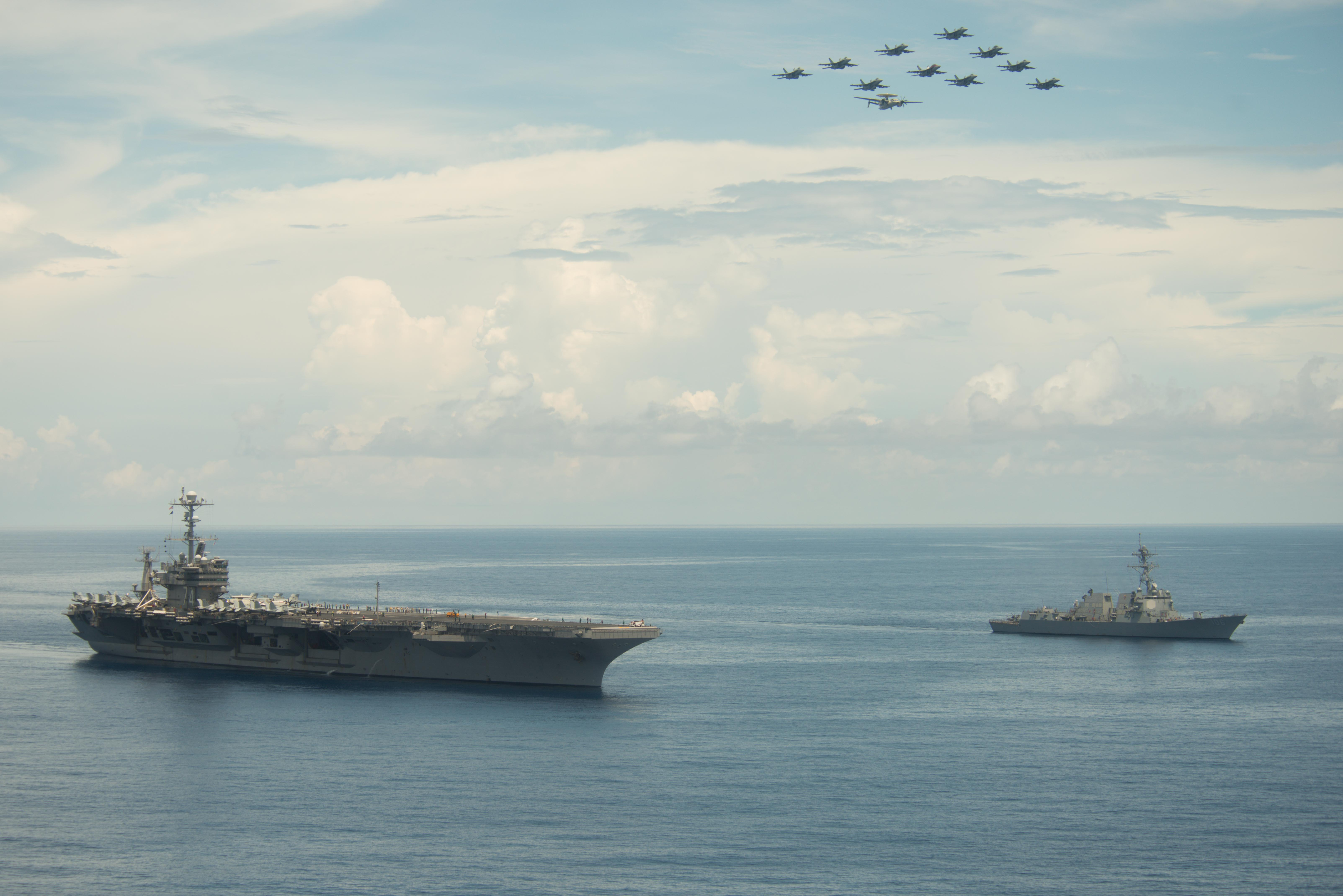 Aircraft assigned to Carrier Air Wing (CVW) 9 fly in formation above USS John C. Stennis (CVN 74) and the guided-missile destroyer USS Stockdale (DDG 106) during an air-and-sea-power demonstration in the South China Sea on May 17, 2016. US Navy photo.
