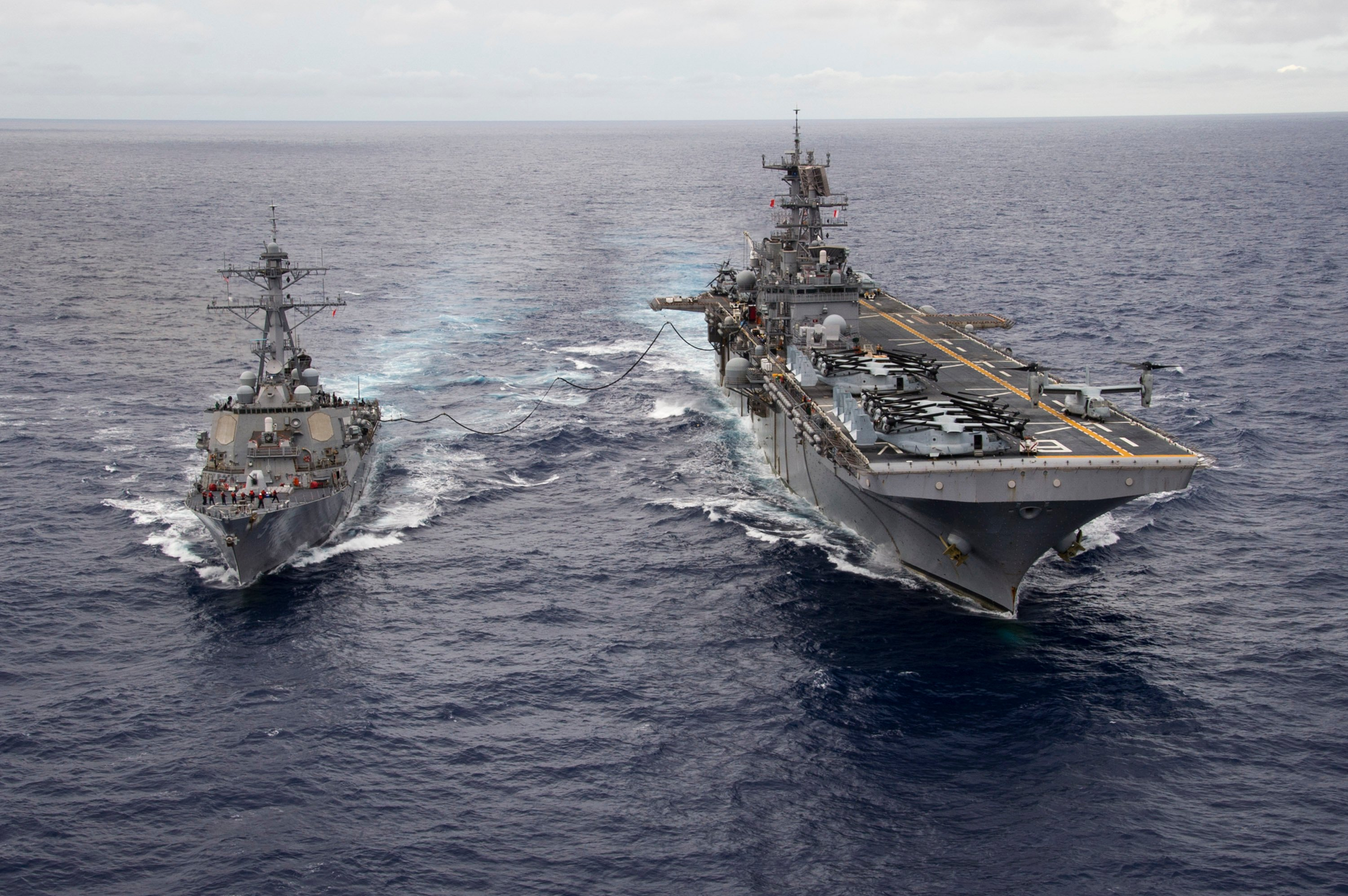 The Arleigh Burke-class guided-missile destroyer USS Curtis Wilber (DDG 54) steams alongside amphibious assault ship USS Bonhomme Richard (LHD 6) in the Philippine Sea Sept. 15 during a fueling at sea (FAS). US Navy photo.