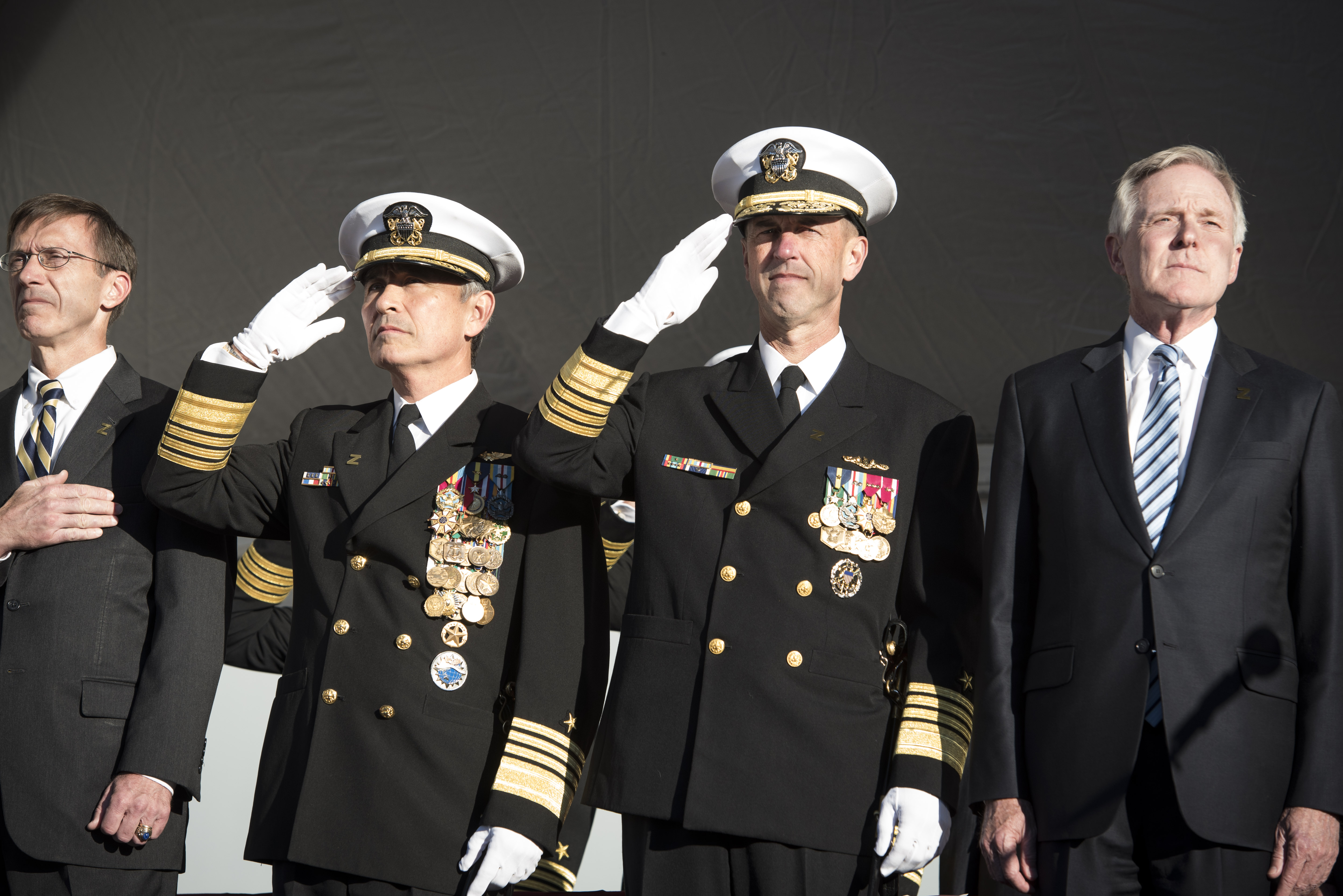 Left to right, Assistant Secretary of the Navy for Research, Development and Acquisition Sean Stackley; Commander, U.S. Pacific Command Adm. Harry Harris; Chief of Naval Operations Adm. John Richardson; and Secretary of the Navy Ray Mabus render honors for the national anthem during the commissioning ceremony for the Navy's newest and most technologically advanced warship, USS Zumwalt (DDG 1000). US Navy photo.