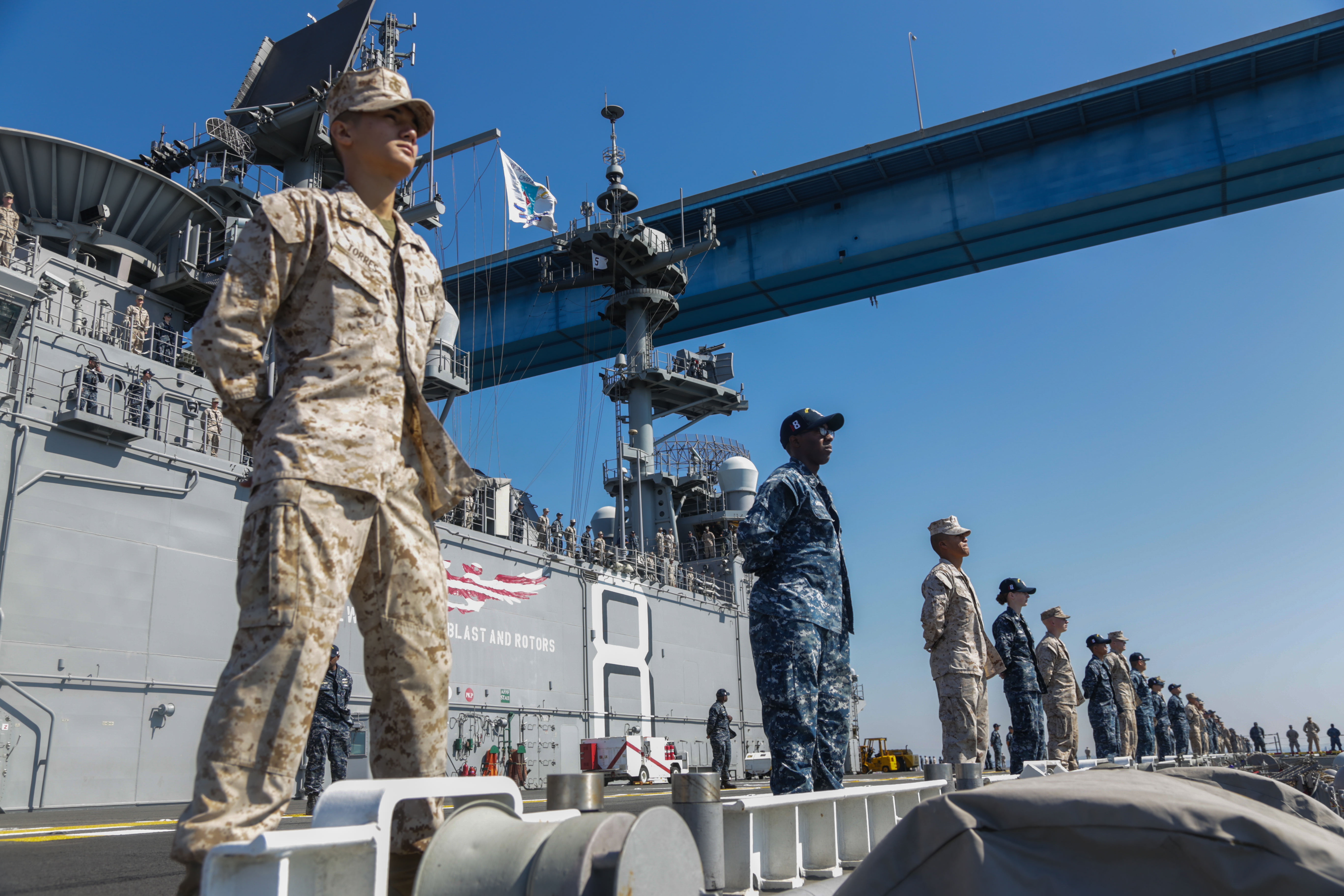 Marines and sailors stand at parade rest while manning the rails of the amphibious assault ship USS Makin Island (LHD-8) on Oct. 14, 2016. US Marine Corps Photo