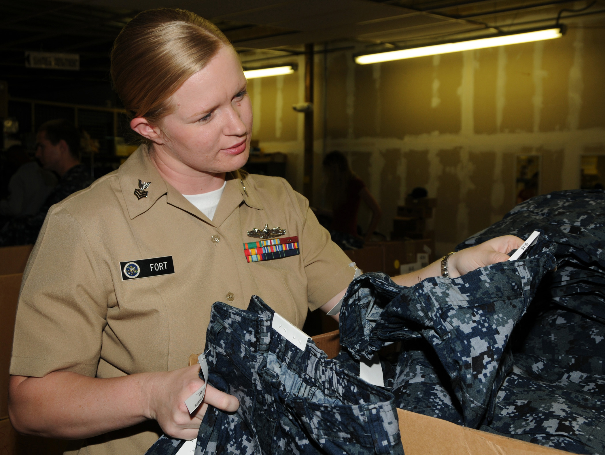 Cryptologic Technician (Collection) 1st Class Wendy Fort looks through the different components of the Navy Working Uniform (NWU) at the Naval Station Pearl Harbor Uniform Center in 2009. US Navy Photo