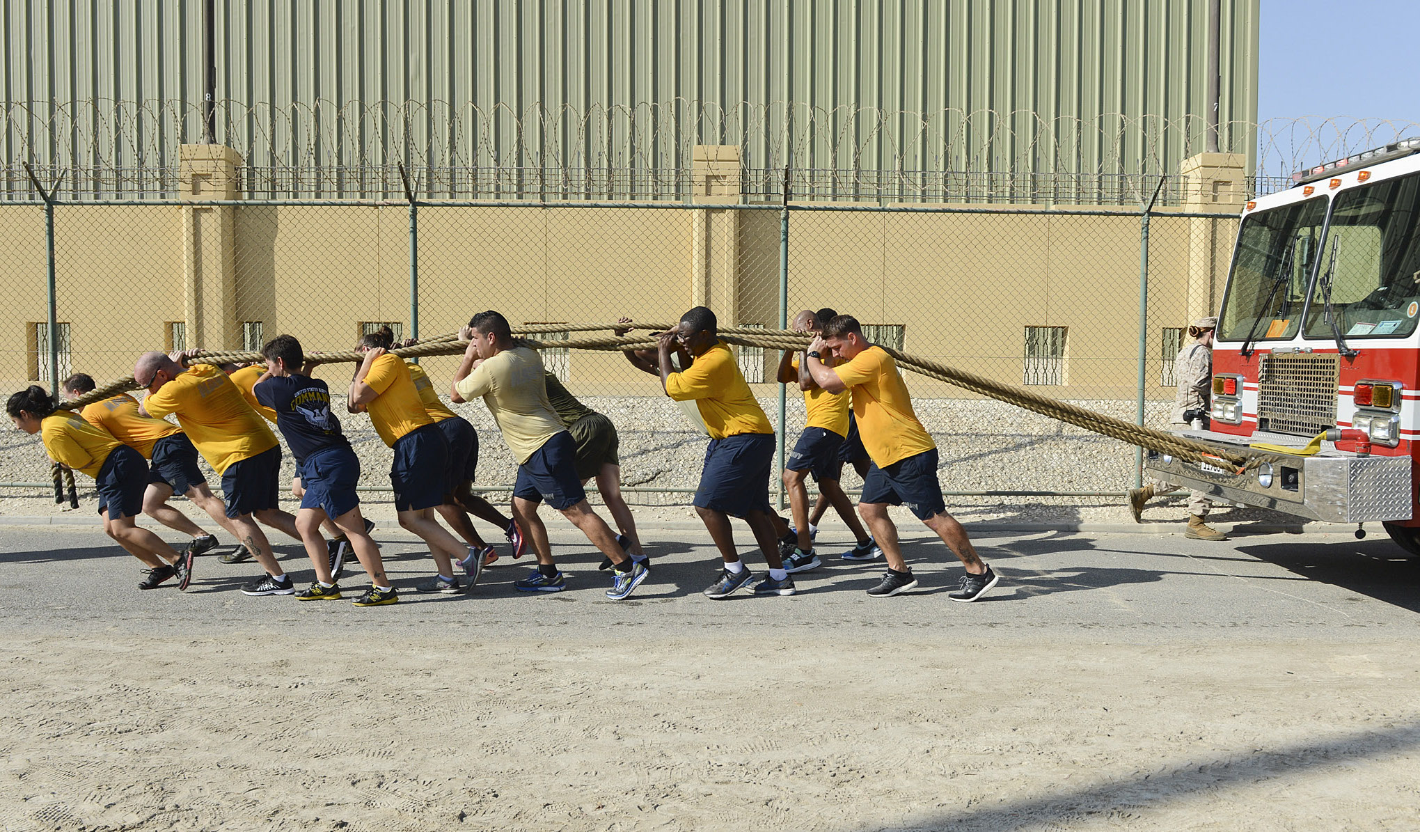 U.S. Sailors, Marines, Soldiers, and Coast Guardsmen stationed aboard Naval Support Activity Bahrain join together in pulling a fire truck during an integrated physical training event. US Navy Photo