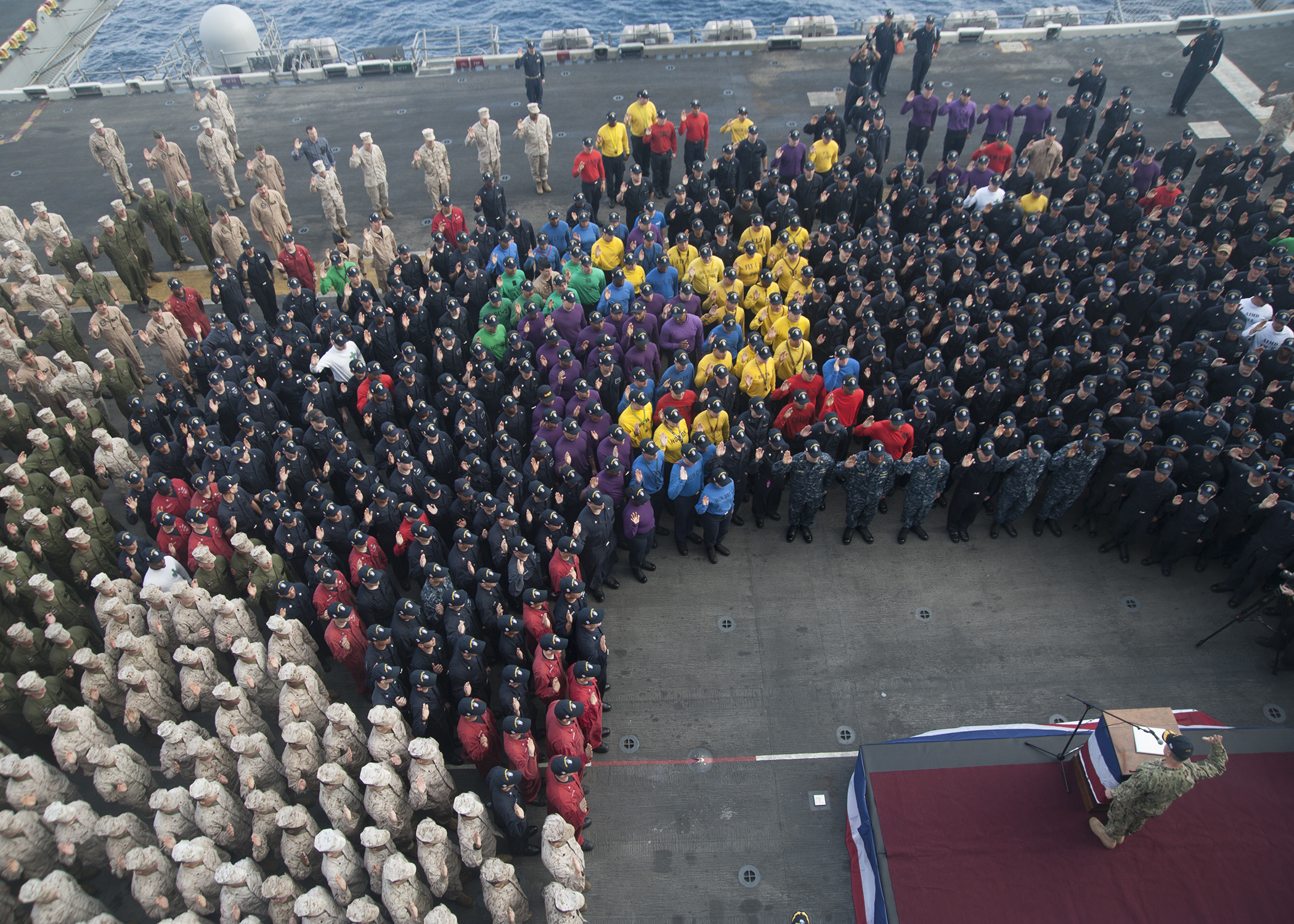 Vice Chief of Naval Operations Adm. Bill Moran delivers the oath of enlistment to Sailors and Marines aboard the amphibious assault ship USS Makin Island (LHD-8) on Dec. 11, 2016. US Navy Photo