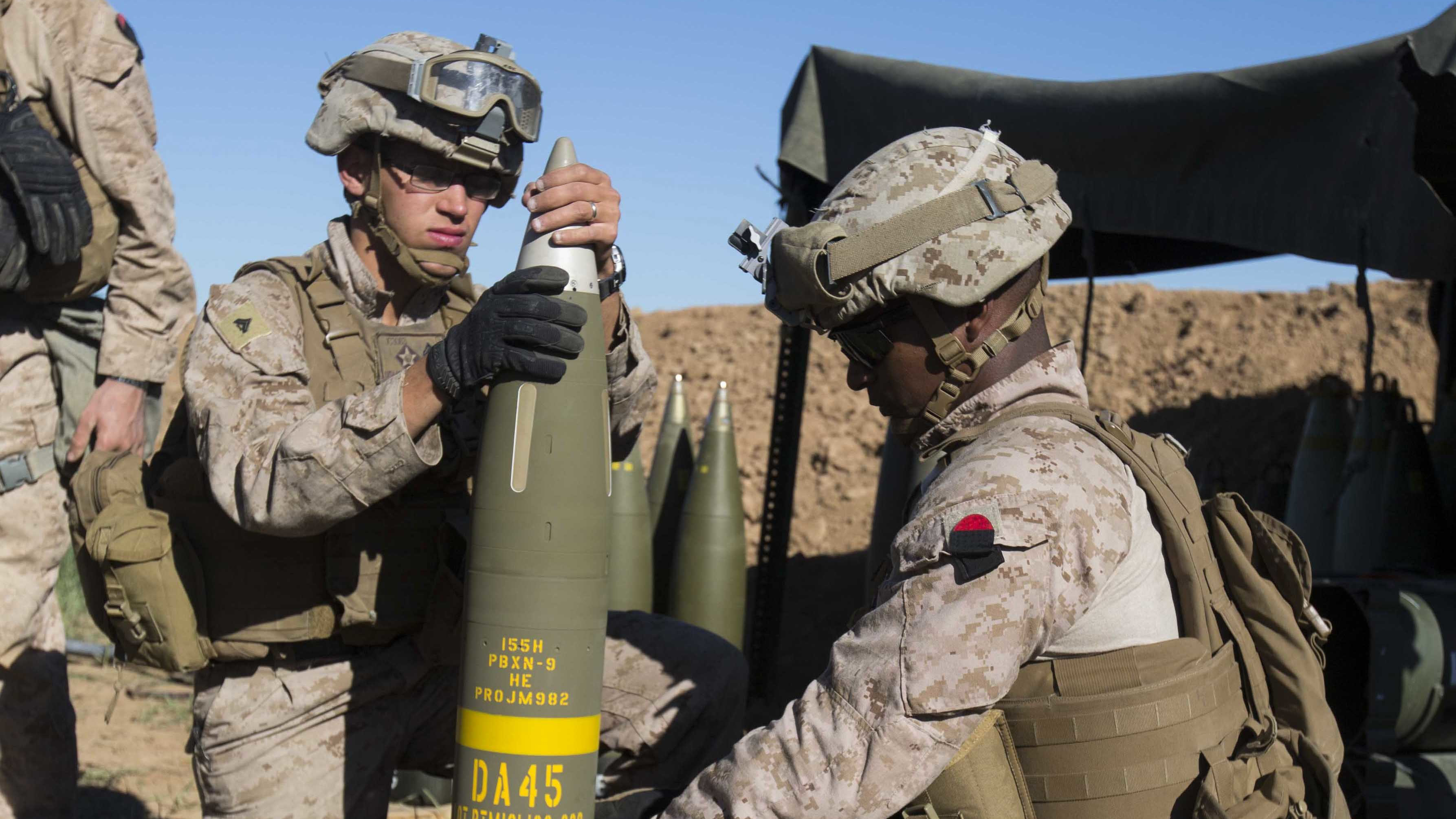 Marines prepare an Excalibur 155 mm projectile round on Fire Base Bell, Iraq, while conducting fire missions on March 18, 2016. US Marine Corps