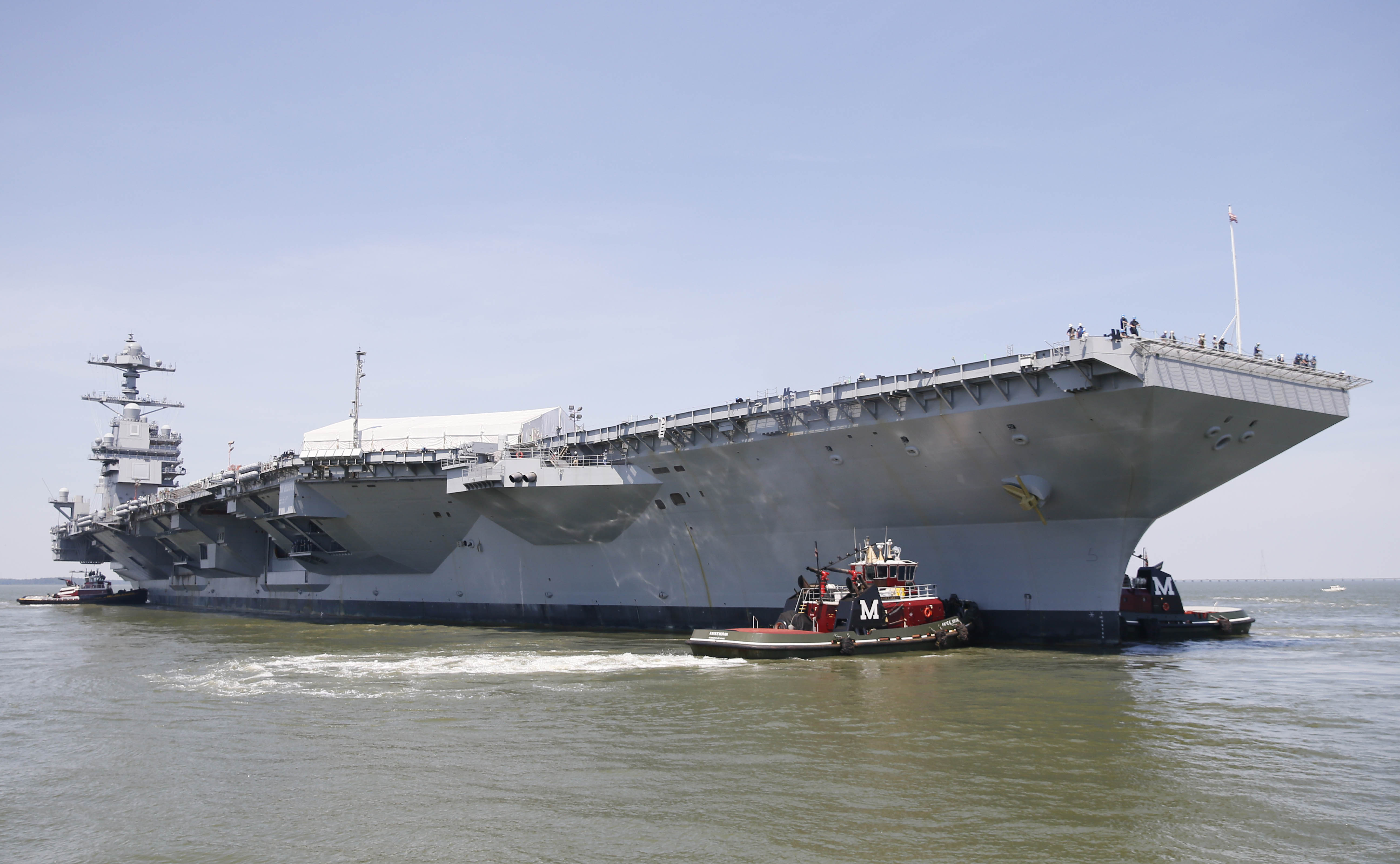 Tug boats maneuver the aircraft carrier Pre-Commissioning Unit Gerald R. Ford (CVN 78) into the James River during the ship's turn ship evolution June 11, 2016. US Navy Photo