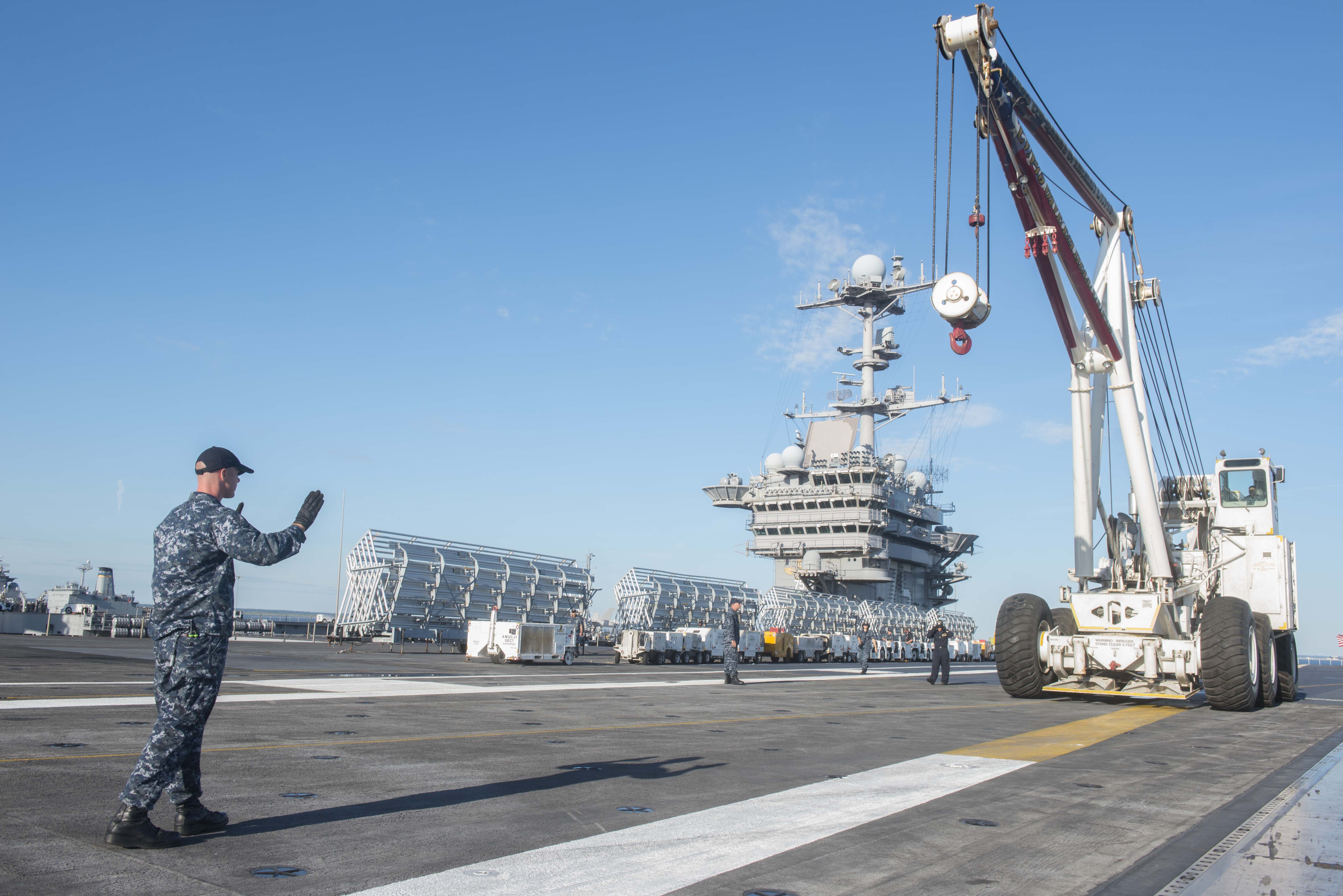 Aviation Boatswain's Mate (Handling) 1st Class Michael Osborne directs the offload process for the mobile crash crane on the flight deck of aircraft carrier USS Harry S. Truman (CVN-75). US Navy Photo