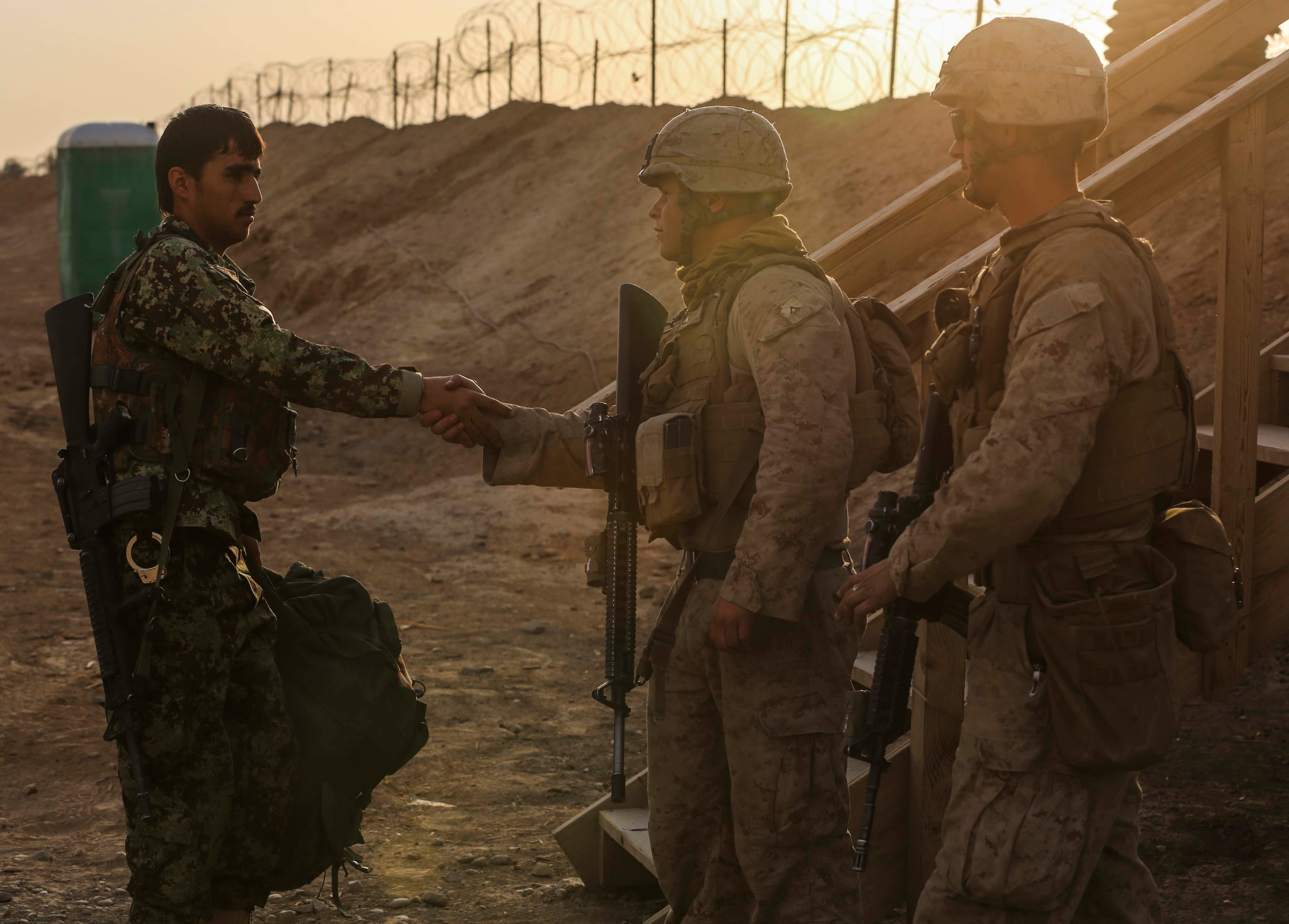 U.S. Marines with Alpha Company, 1st Battalion, 2d Marine Regiment, greet a member of the Afghanistan National Army (ANA) as he takes his post aboard Camp Leatherneck, Helmand Province, Afghanistan on October 27, 2014. The ANA will took command of all posts aboard Camp Leatherneck upon the end of Regional Command (Southwest) operations in Helmand province. US Marine Corps photo.