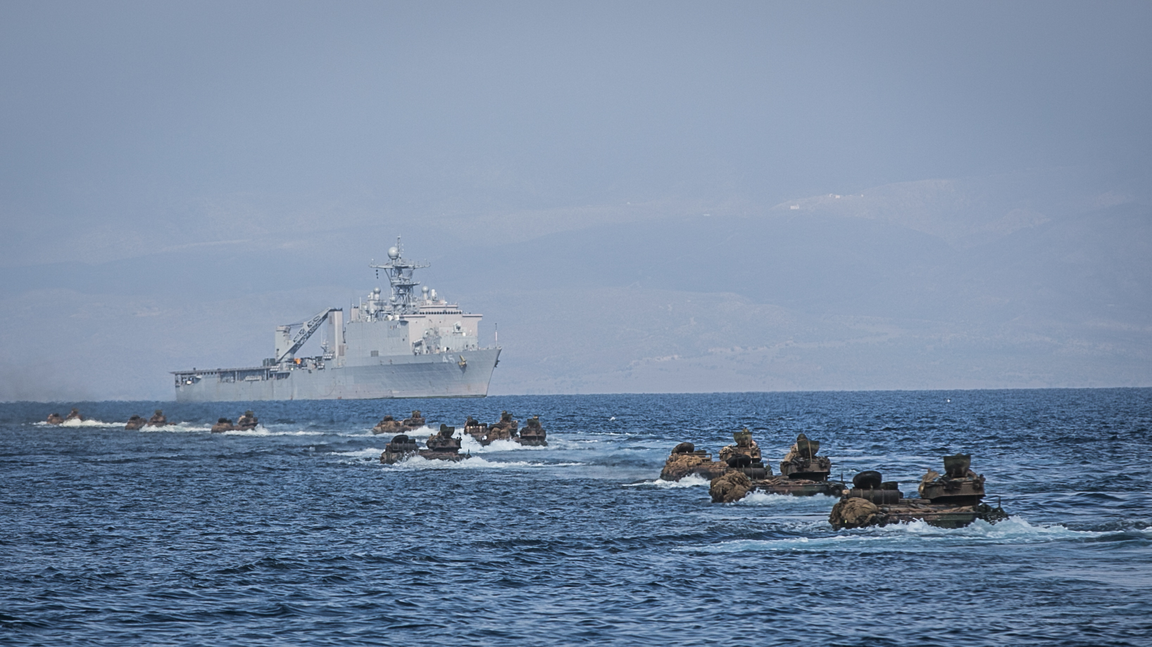 U.S. Marines with Battalion Landing Team, 1st Battalion, 4th Marines, 11th Marine Expeditionary Unit (MEU), advance toward the dock landing ship USS Comstock (LSD 45) via amphibious assault vehicles (AAV) after completing training for Exercise Alligator Dagger at Arta Beach, Djibouti, Dec. 21, 2016. US Marine Corps Photo