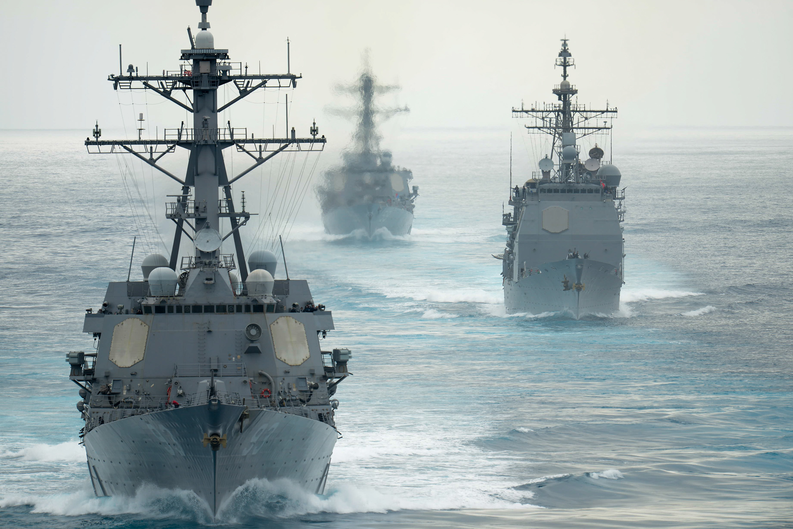 The guided-missile destroyers USS Russel (DDG 59), USS Chung Hoon (DDG 93) and the guided-missile cruiser USS Mobile Bay (CG 53) follow the aircraft carrier USS John C. Stennis (CVN 74) during a show of force transit on Aug. 11, 2015. US Navy photo.