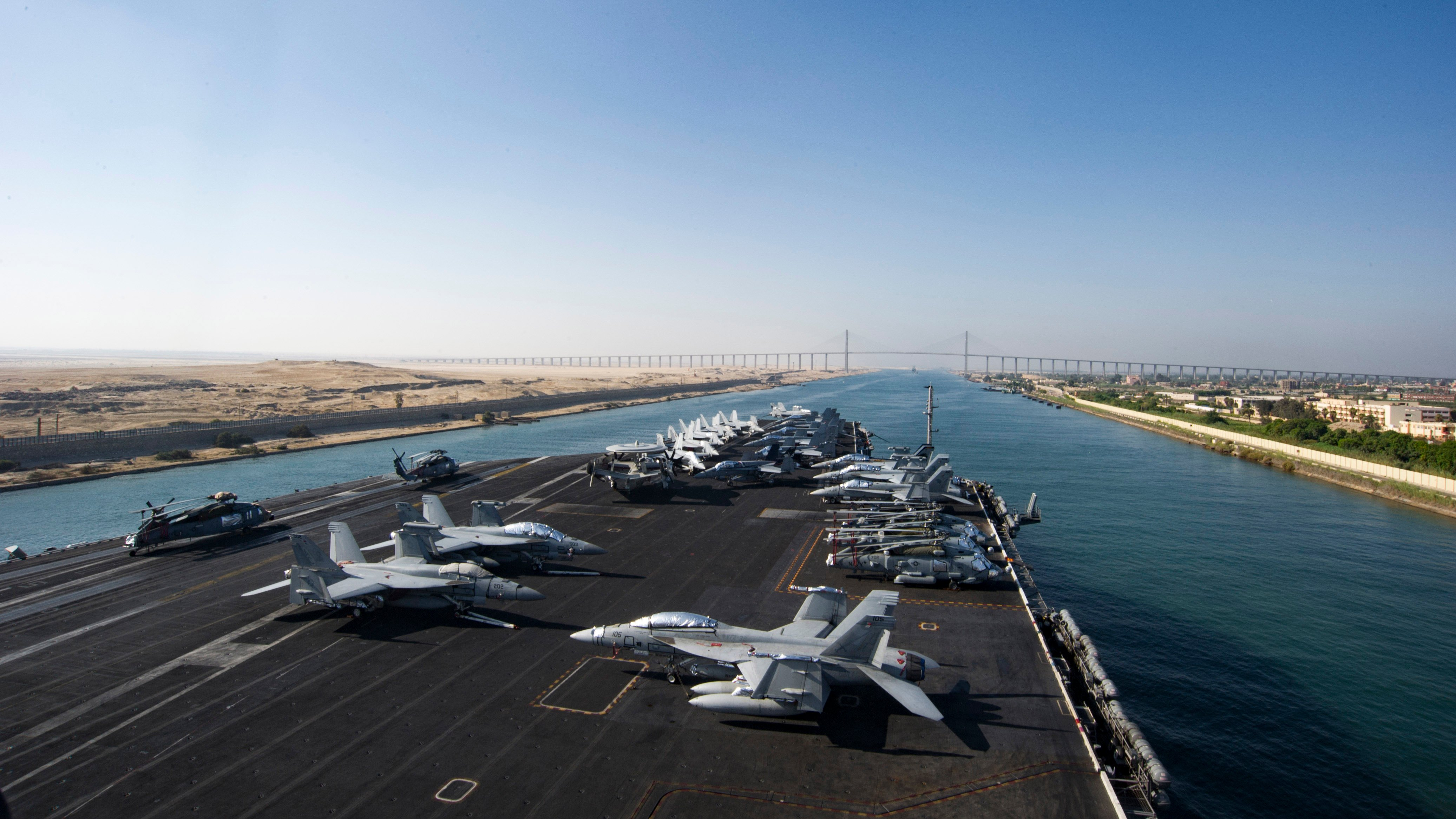 The aircraft carrier USS Dwight D. Eisenhower (CVN 69) approaches the Friendship Bridge as it transits the Suez Canal on July 8, 2016. The Eisenhower Carrier Strike Group was deployed in support of maritime security operations and theater security cooperation efforts in the U.S. 5th and 6th Fleet area of operations. US Navy photo.
